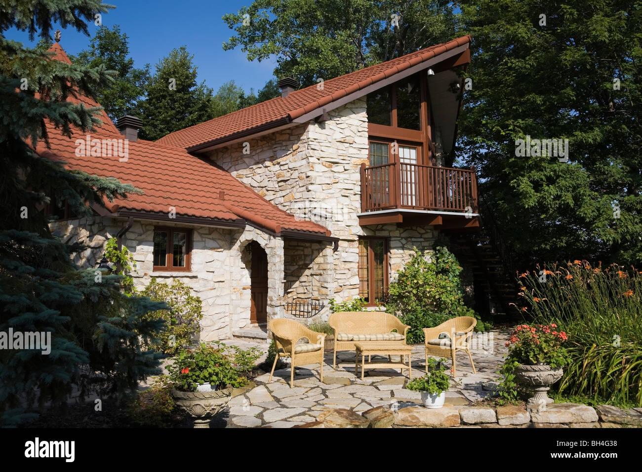 Home con paesaggistici cortile anteriore e un arredamento in vimini sul patio, Laval, Québec Immagini Stock