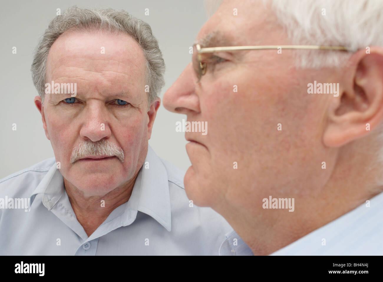 Close up ritratto di due alti uomini con espressioni gravi Immagini Stock