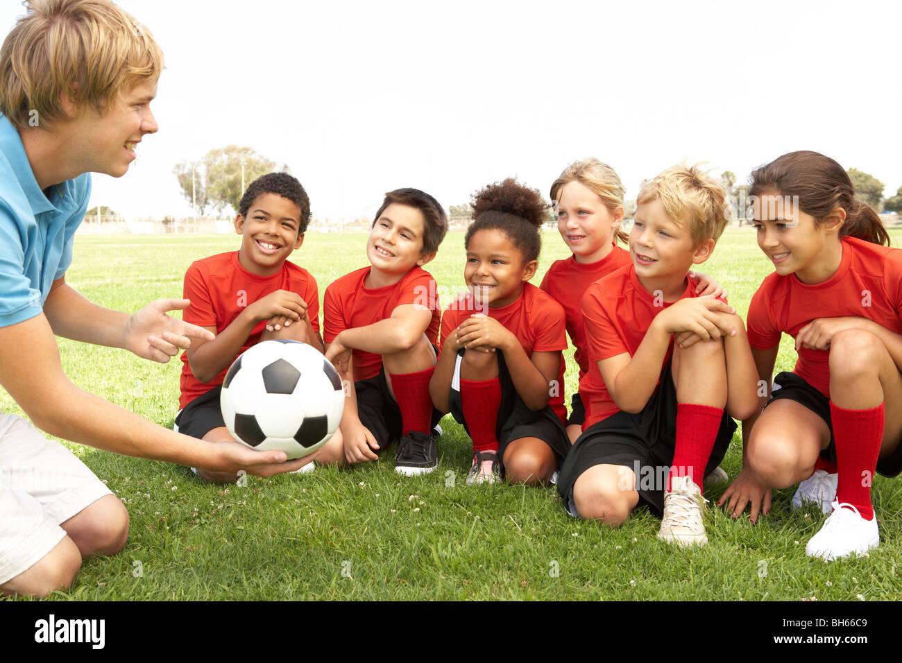 I ragazzi e le ragazze nella squadra di calcio con pullman Immagini Stock
