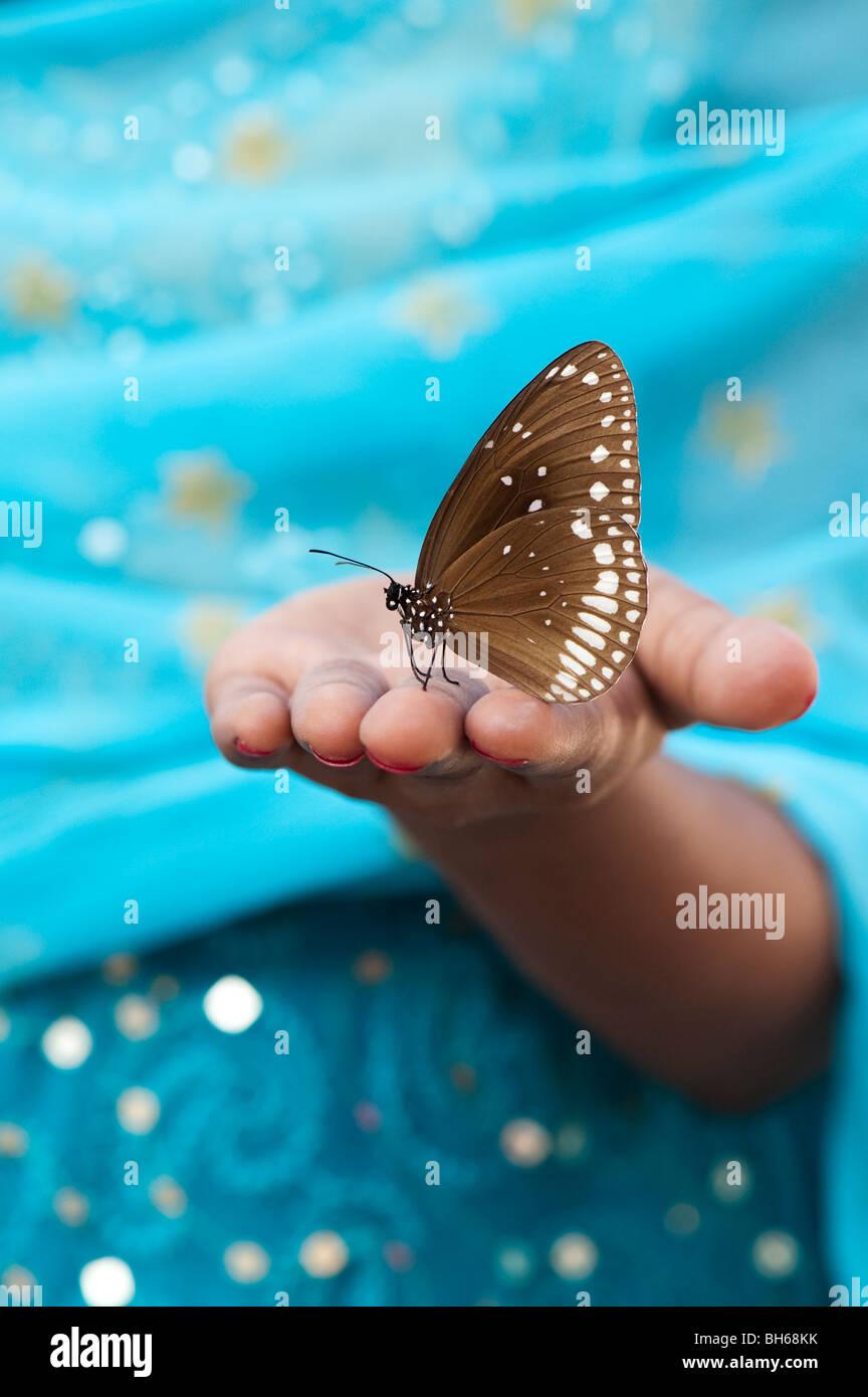 Euploea core. Il corvo comune farfalla sulla mano di una ragazza indiana. Andhra Pradesh. India Immagini Stock