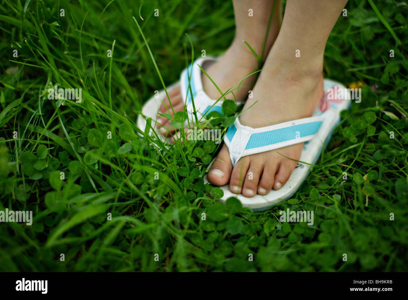 6 anno vecchia ragazza con flip flop di erba Immagini Stock