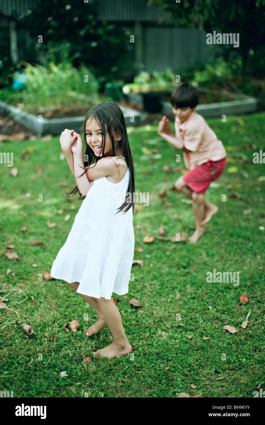 Un ragazzo e una ragazza pratica yoga in un giardino Immagini Stock