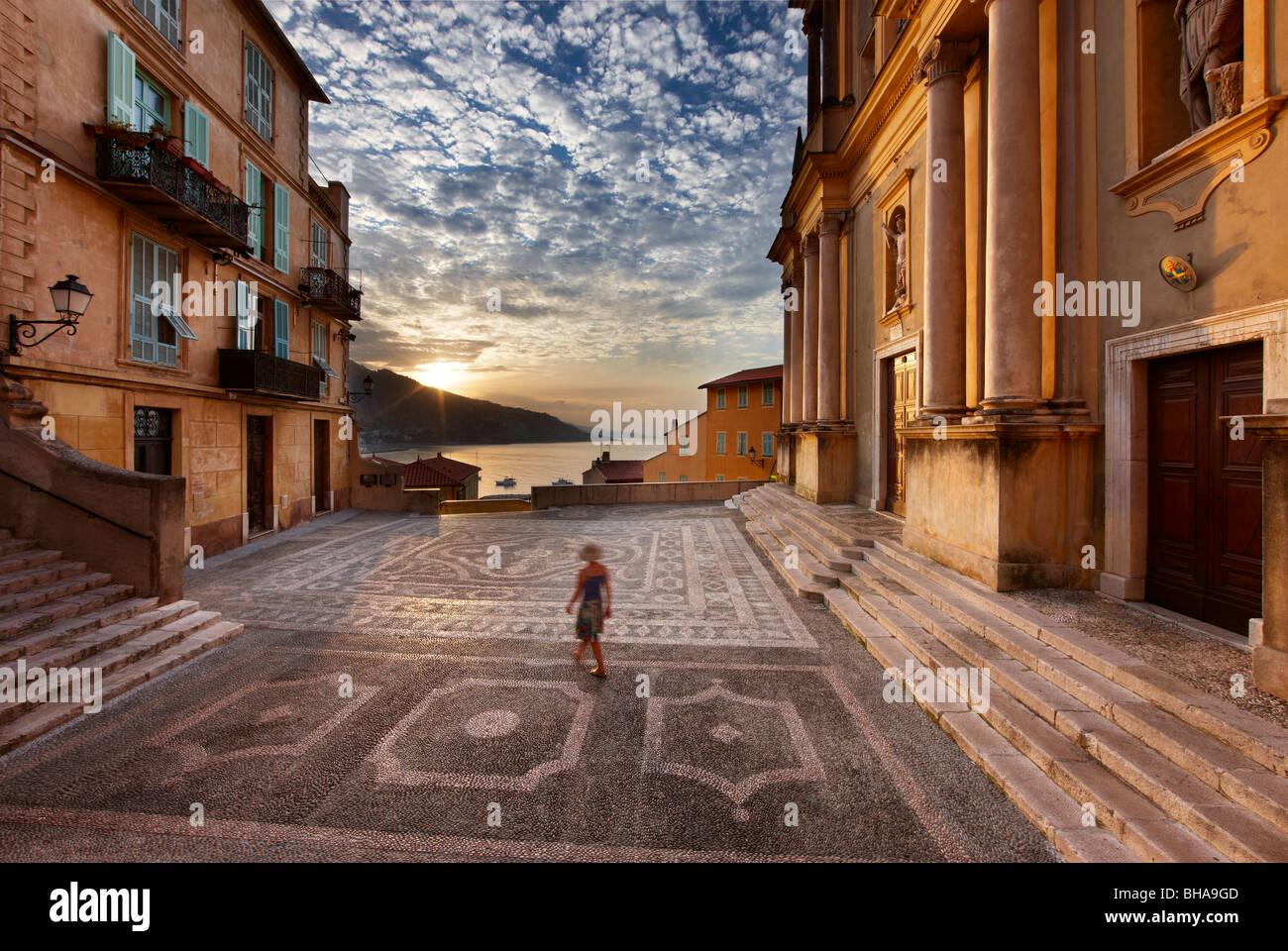 Una donna a piedi attraverso Parvis St Michel all'alba, la Città Vecchia, Menton, Cote d'Azur, alpi Immagini Stock