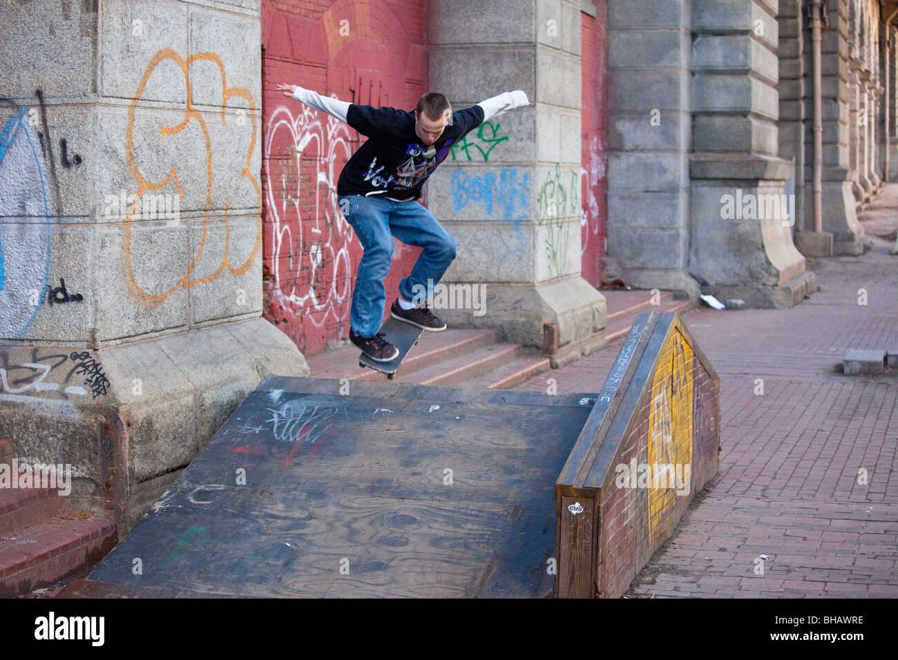 Teen facendo trucchi skateboard a Manhattan, New York City Immagini Stock