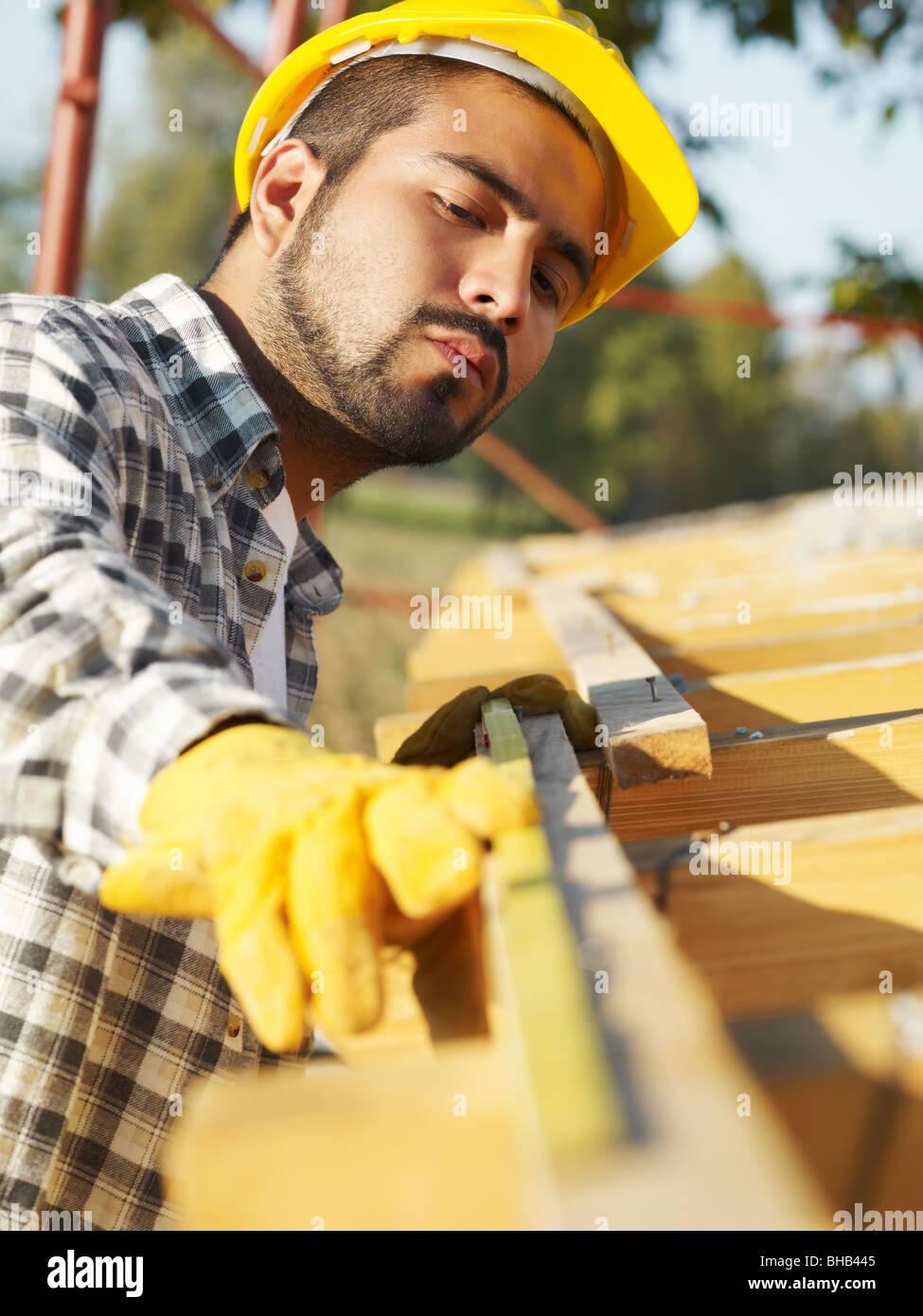 Latin American lavoratore edile sul tetto della casa con nastro di misurazione. Immagini Stock