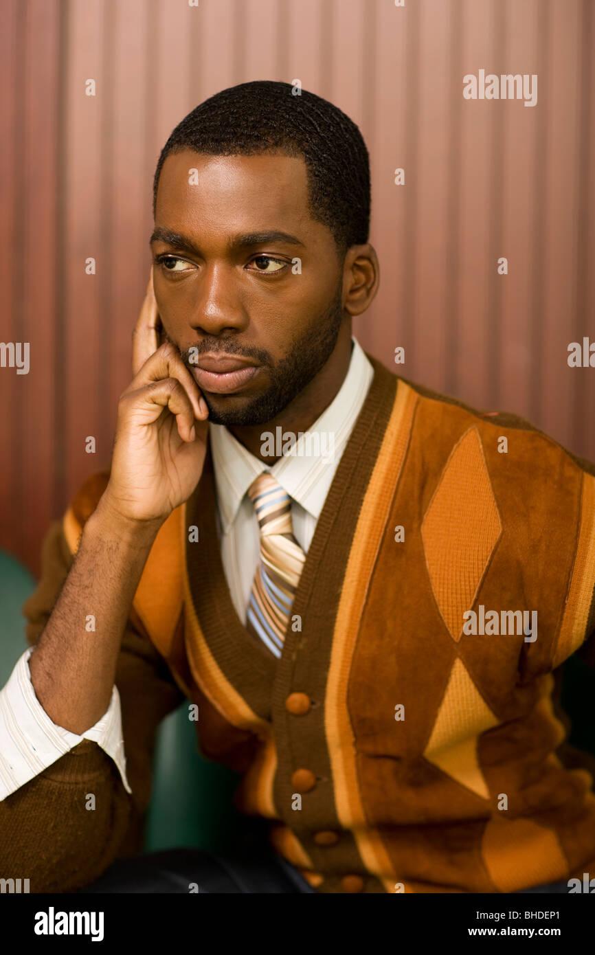 Ben vestito uomo africano guardando pensieroso Foto Stock