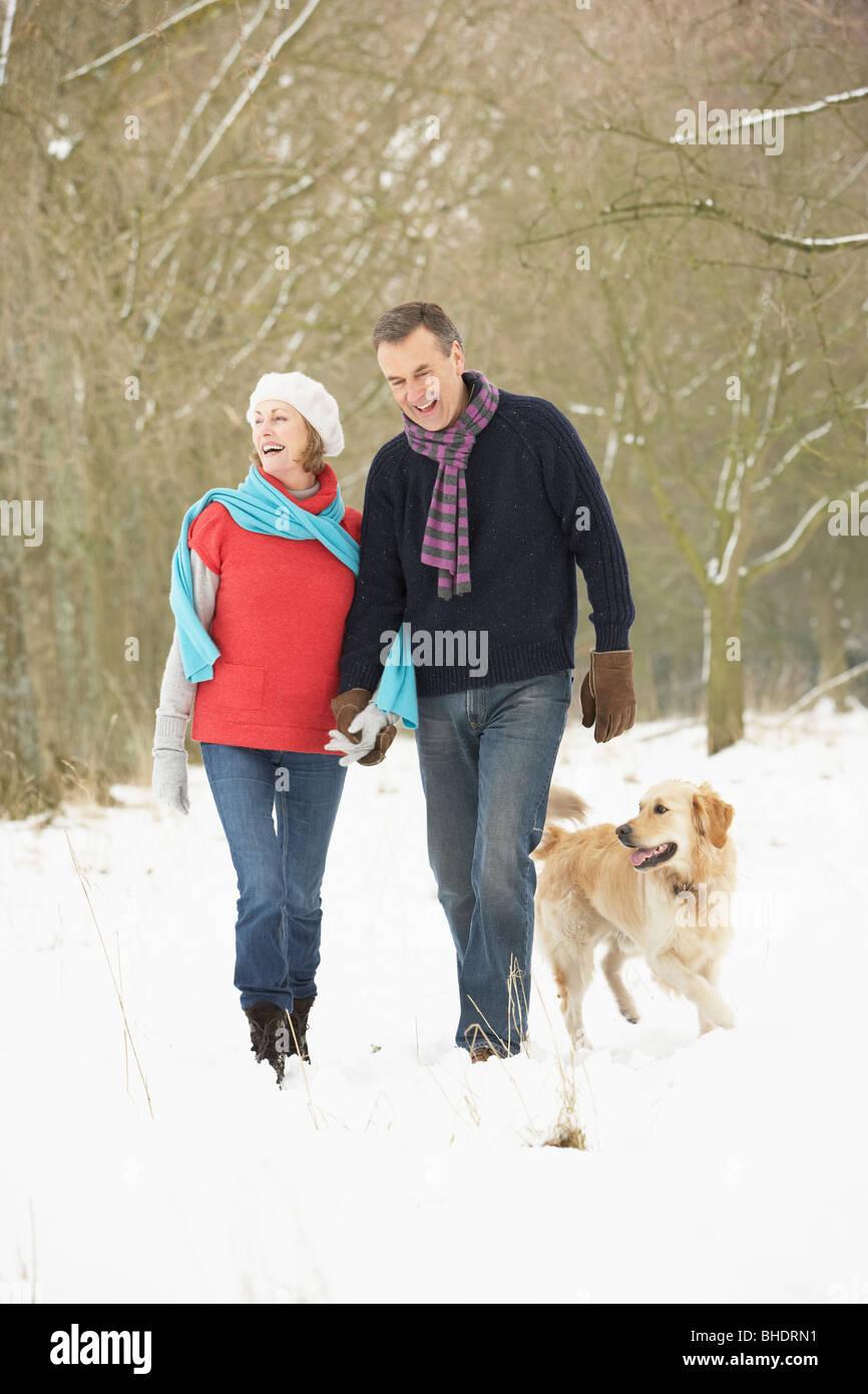 Coppia senior cane a piedi attraverso il bosco innevato Foto Stock