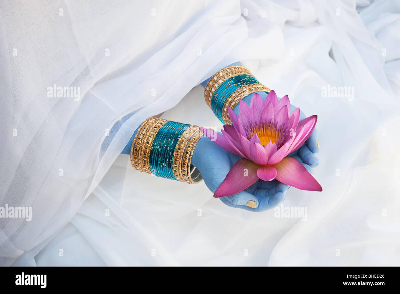 Ragazza indiana offre un Nymphaea tropicale Fiore di ninfea blu con mani dipinte e bracciali. India Immagini Stock