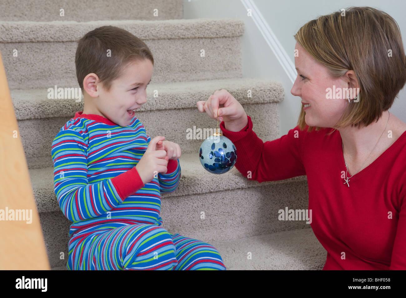 La donna che mostra ornamento di Natale a suo figlio Immagini Stock