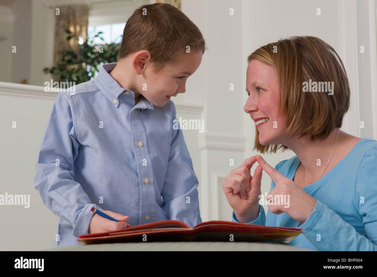 """Donna firma la parola """"parola"""" in American Sign Language insegnamento mentre suo figlio Foto Stock"""