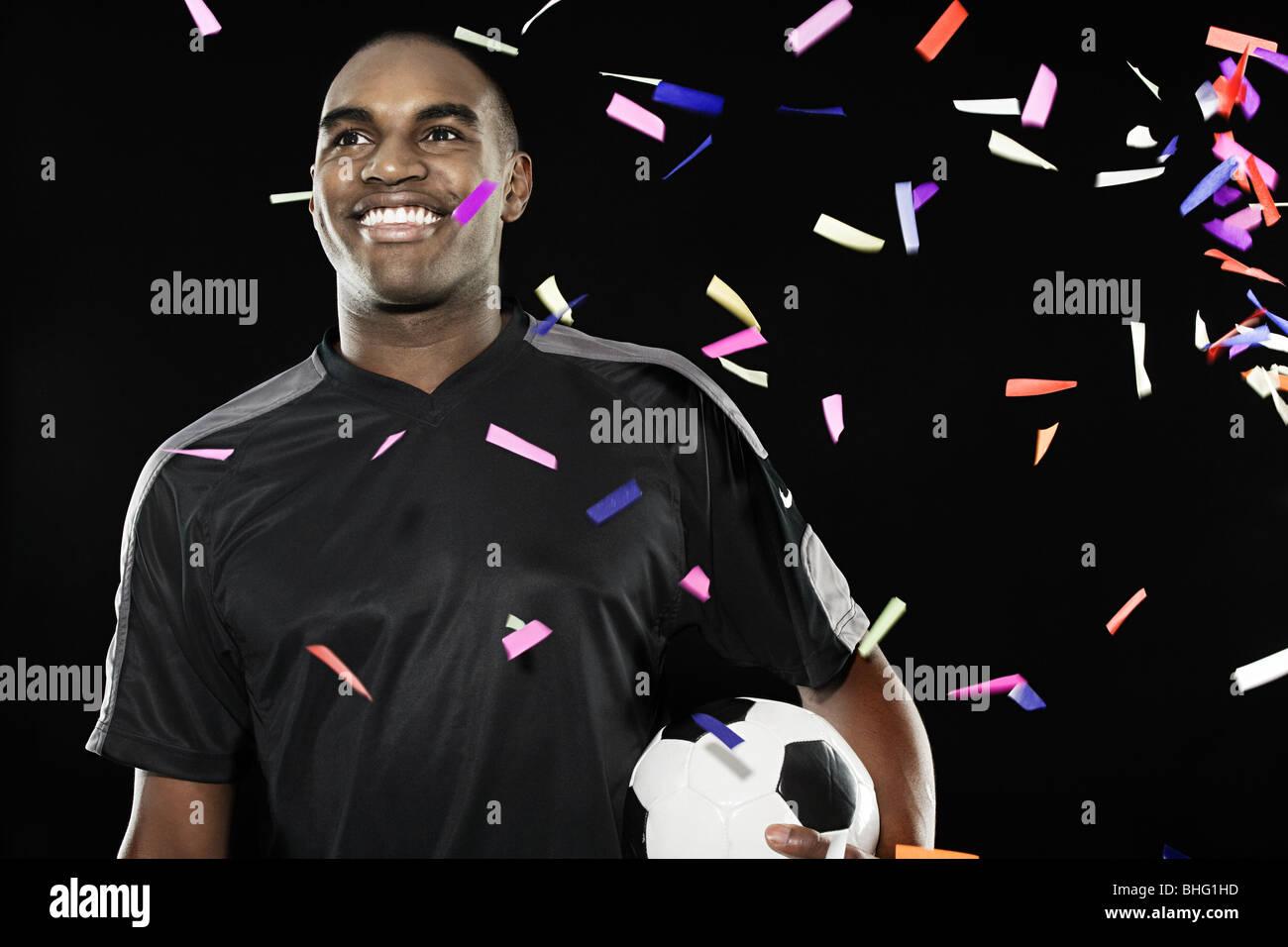 Il calciatore con la caduta di coriandoli Immagini Stock