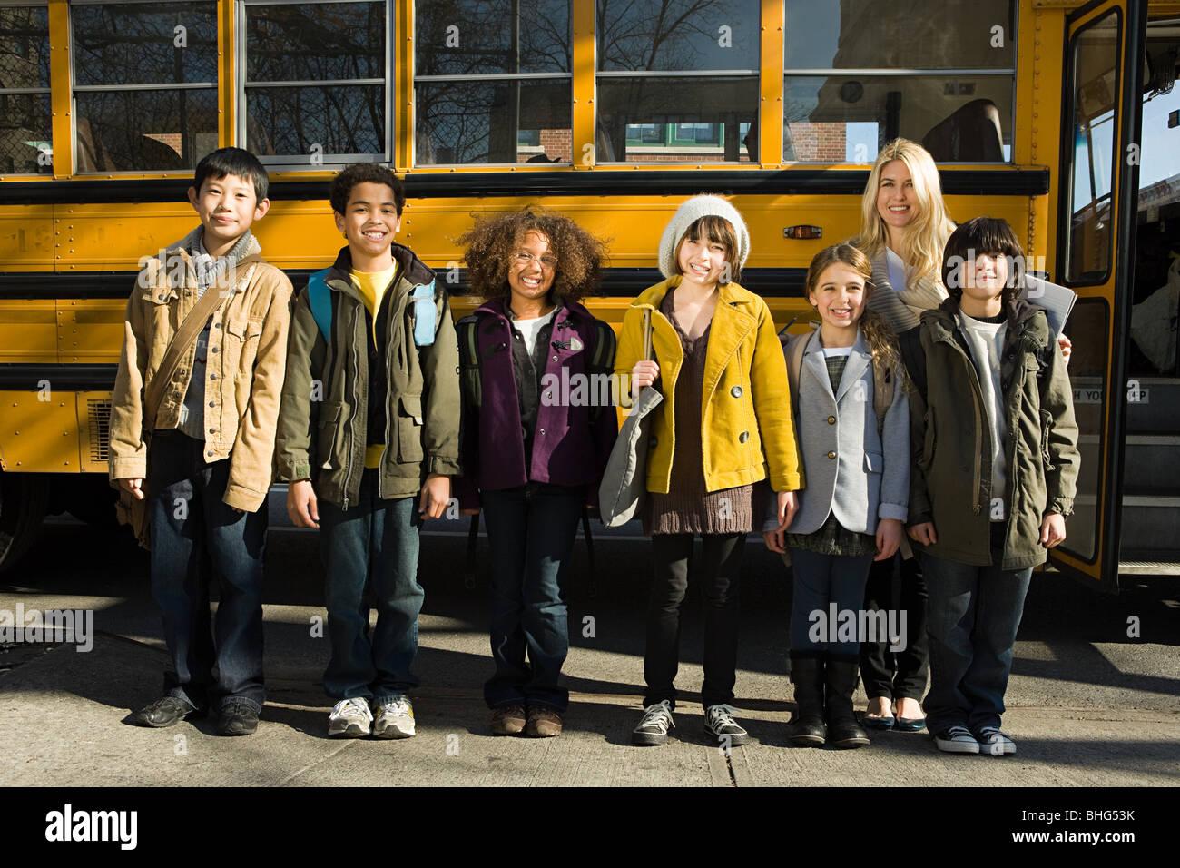 Bambini e insegnante di scuola bus Immagini Stock