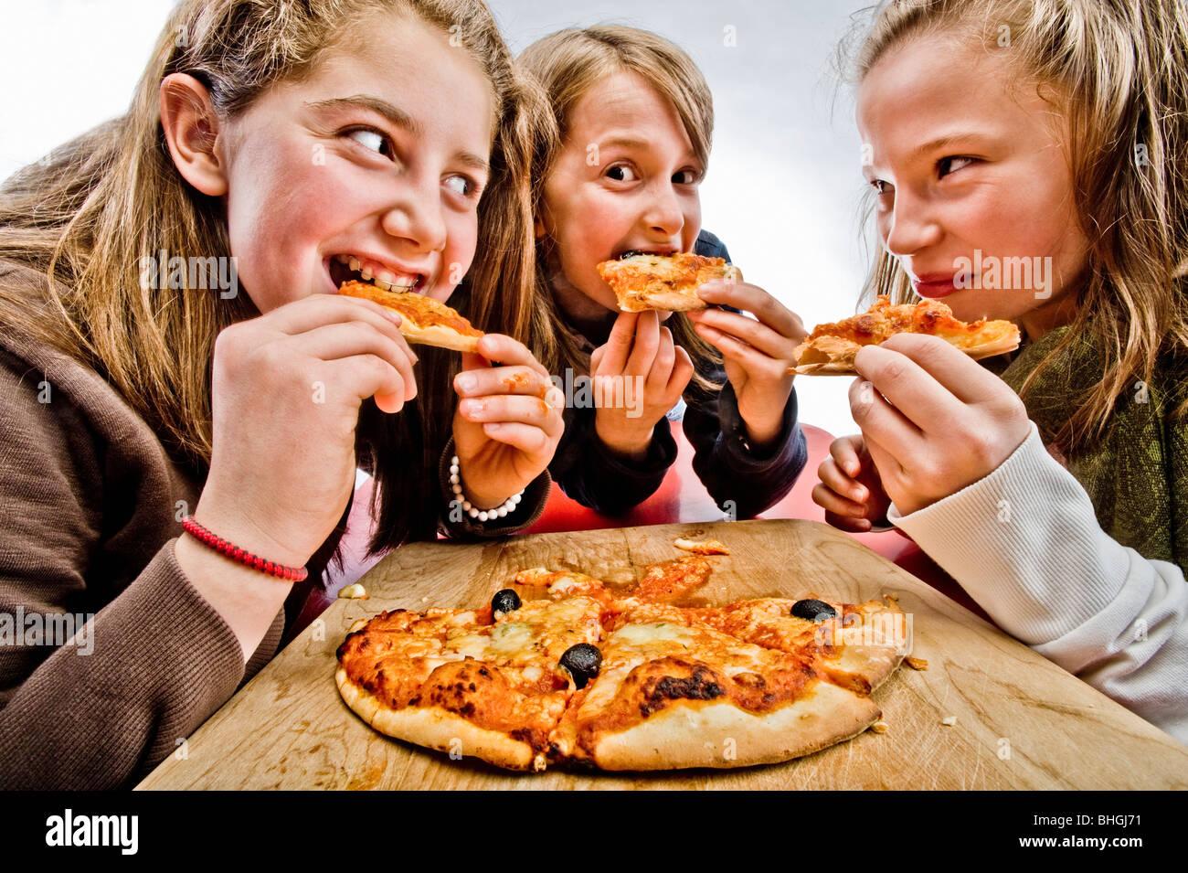3 adolescenti mangiare la pizza Foto Stock