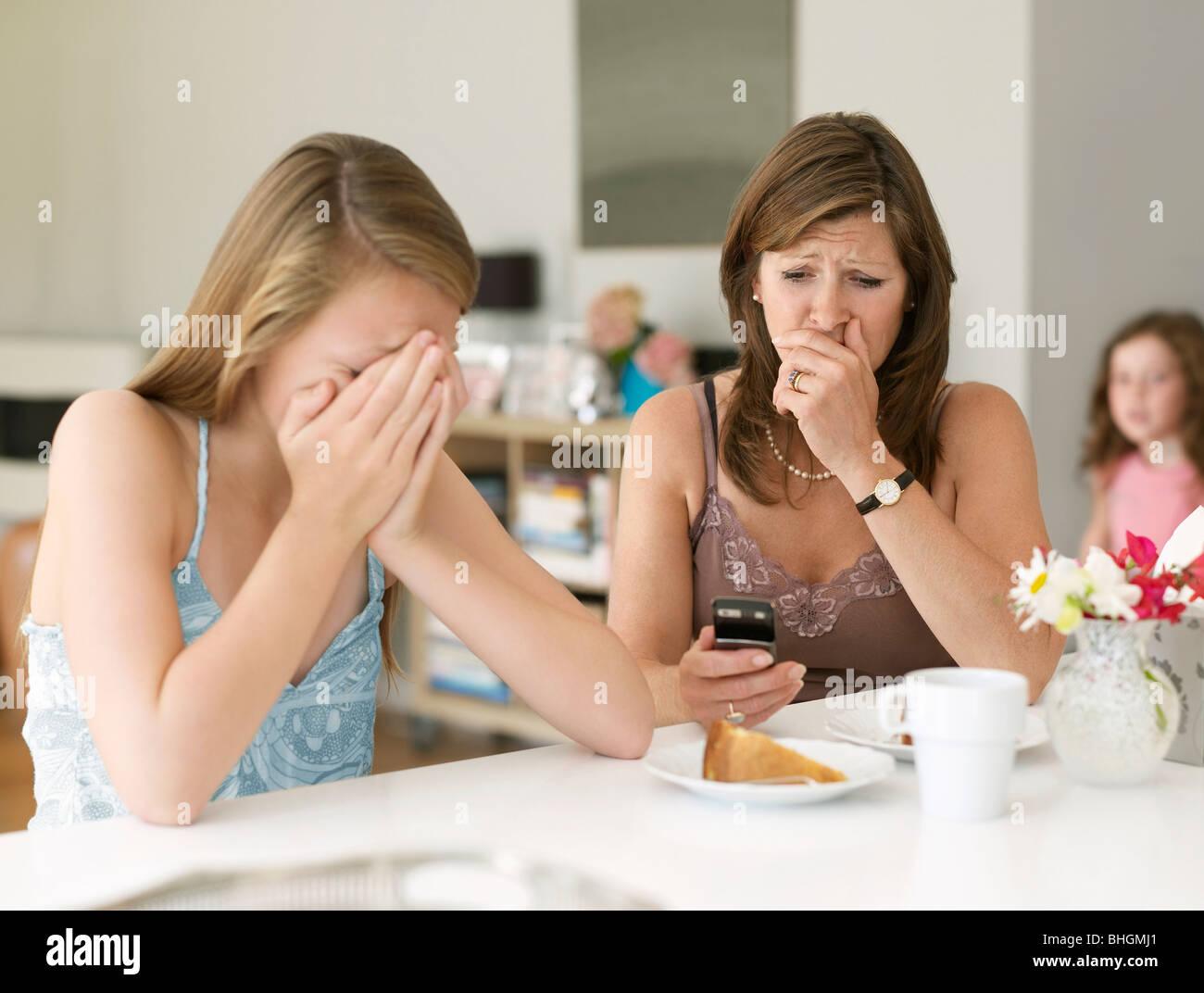 La madre vede il cyber bullismo sul cellulare Immagini Stock