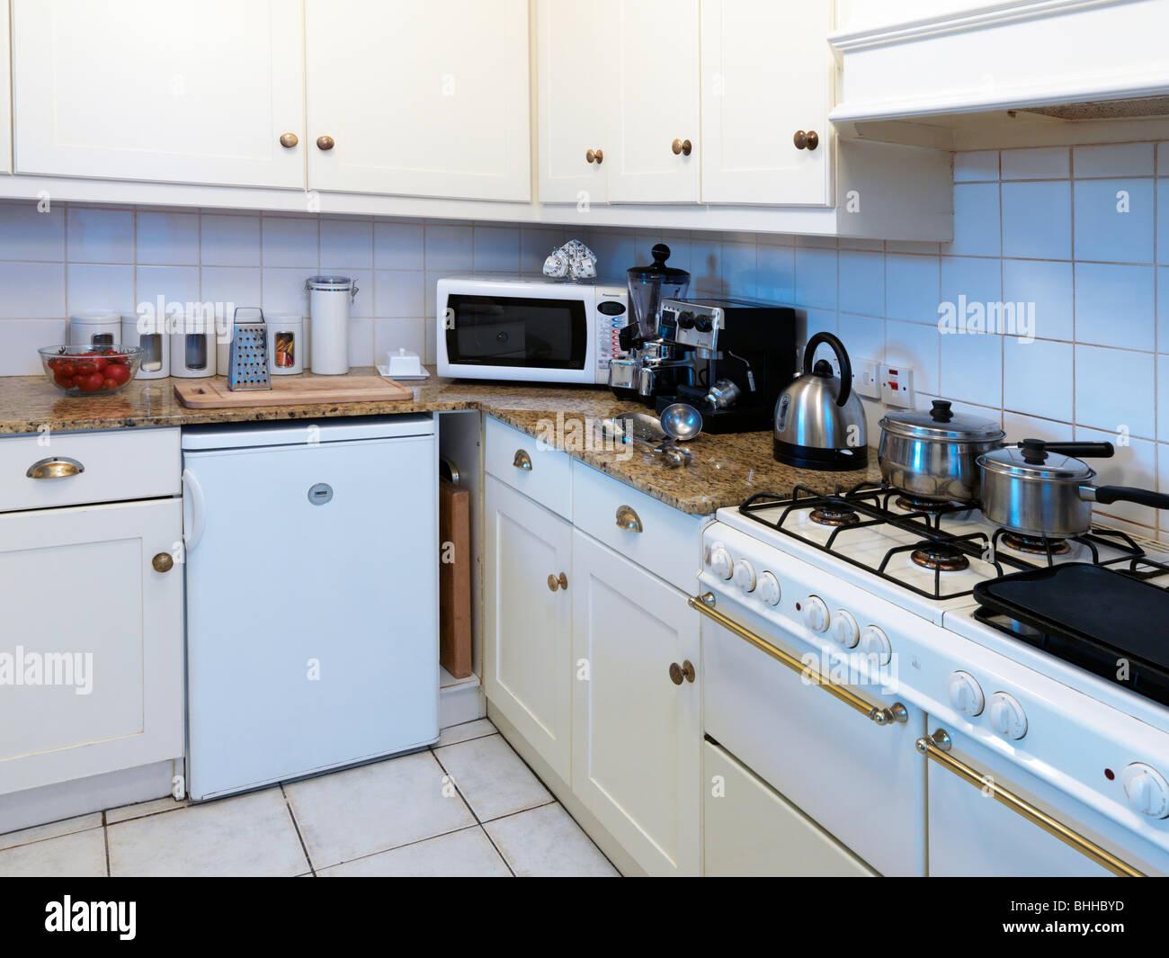 Una cucina con oggetti metallici in vista, frigo, forno, stoviglie ...