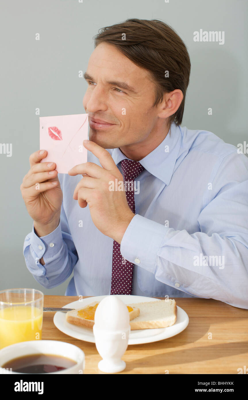 L'uomo prendendo un odore in una lettera d'amore Immagini Stock