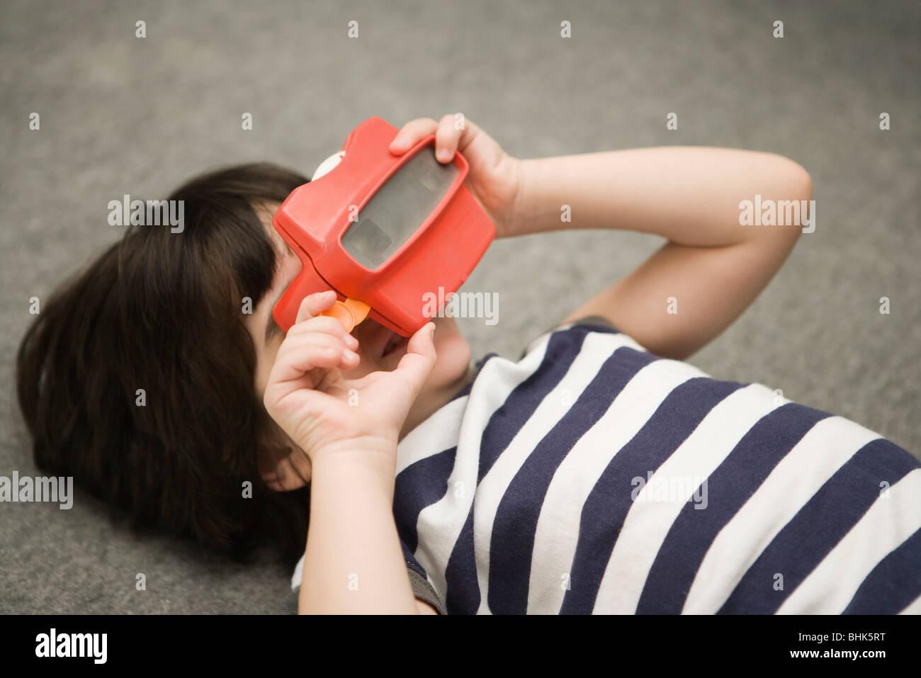Bambino guardando attraverso il mirino del giocattolo Immagini Stock