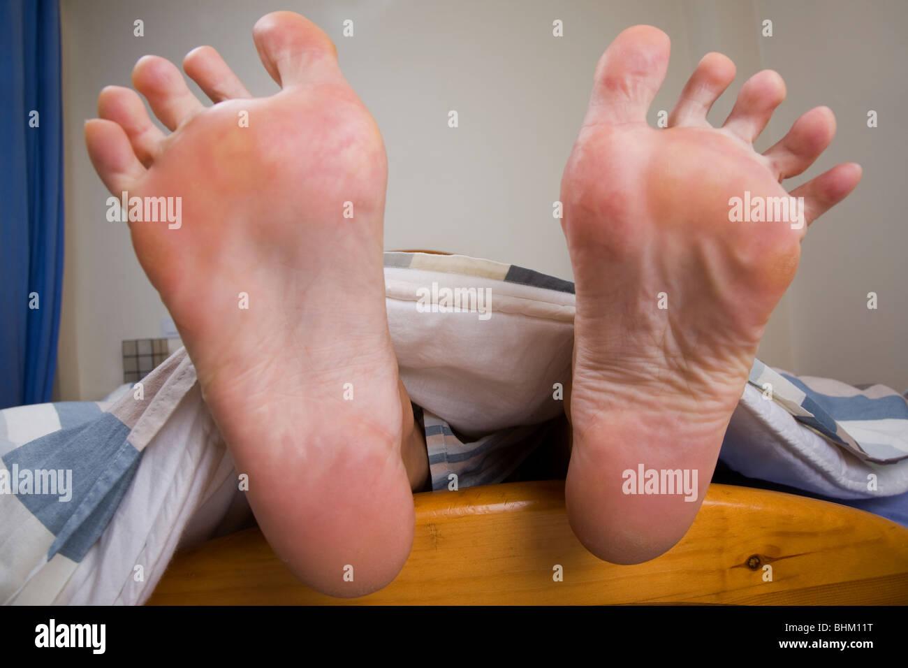 Il piede femminile che sporge dalla estremità di un letto Immagini Stock