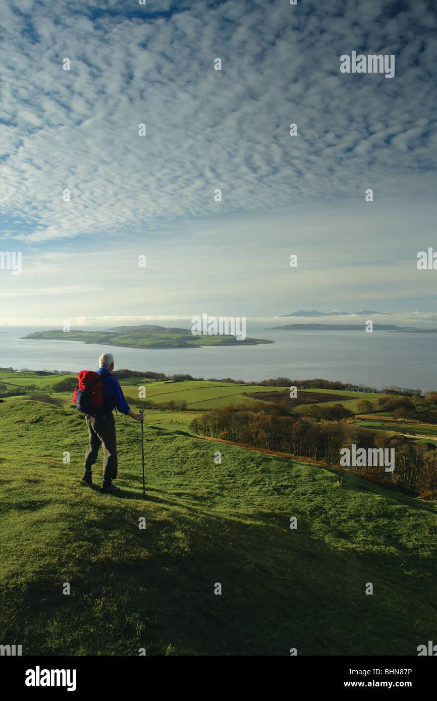 Un viandante guarda verso Arran e Cumbrae dal Knock, un Iron Age Fort sopra Largs sull'Ayrshire sentiero costiero, Scozia Foto Stock