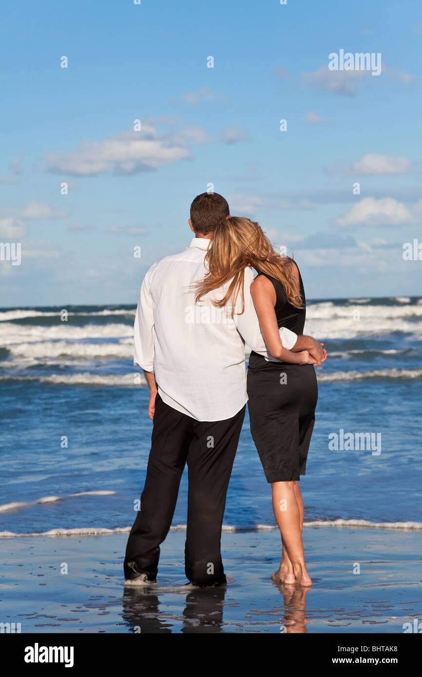 Un giovane uomo e donna coppia romantica in amore braccia attorno a ciascun altro coccole su una spiaggia con un Immagini Stock