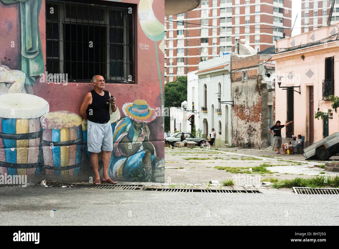 Un uomo sips mate durante la visione di un tamburo di pratica su un angolo della Curuguaty e Carlos Gardel a Montevideo, Immagini Stock