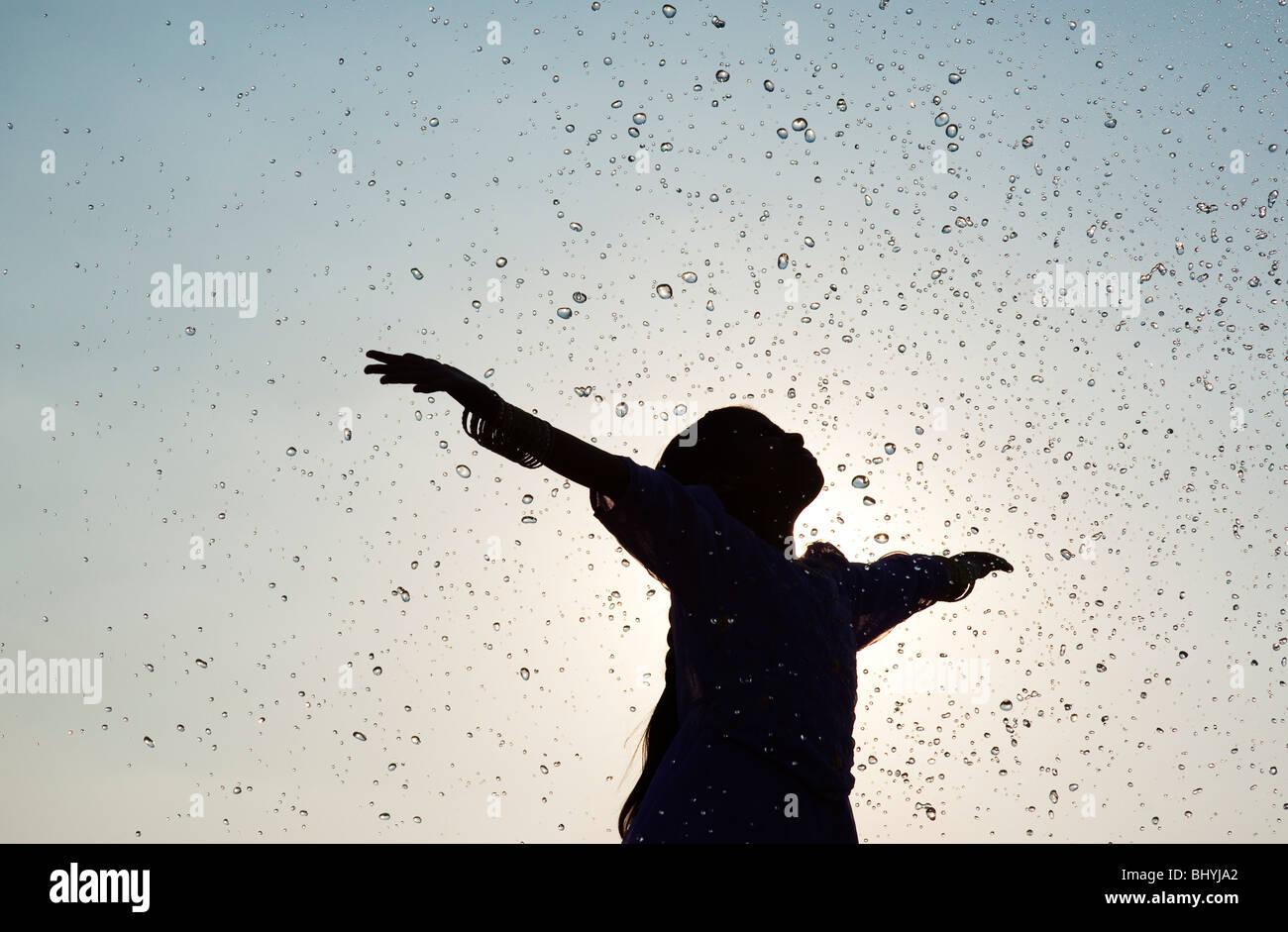 Silhouette di una giovane ragazza indiana godendo di essere spruzzato con acqua Immagini Stock
