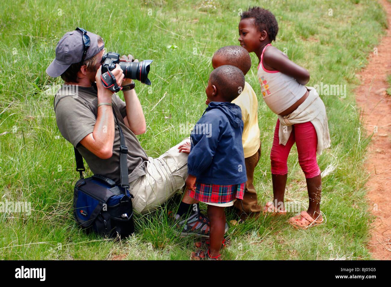 Fotografo in Lesotho con curiosi i bambini Immagini Stock