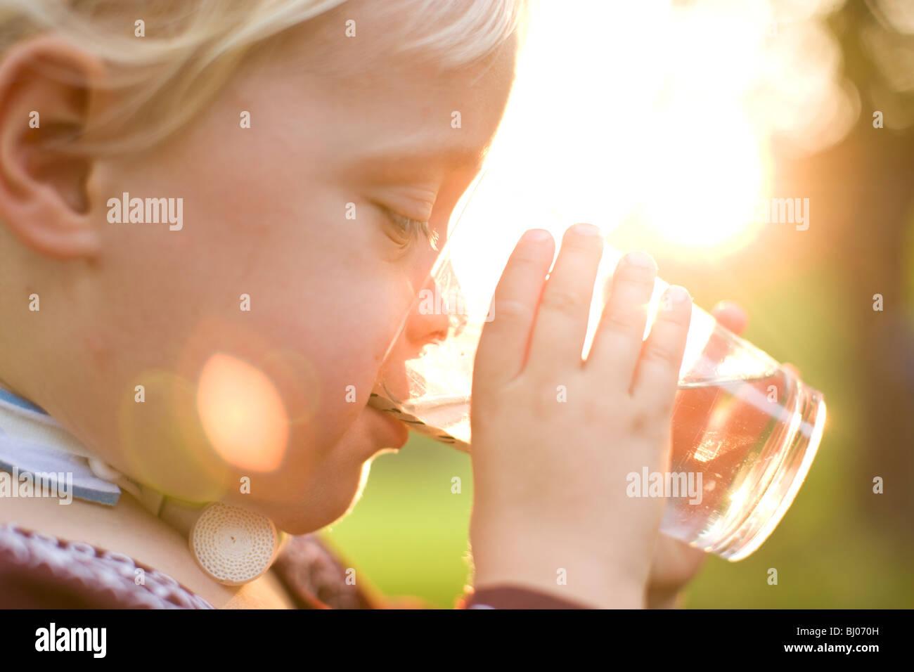 Ragazzo giovane bere un bicchiere d'acqua. Immagini Stock