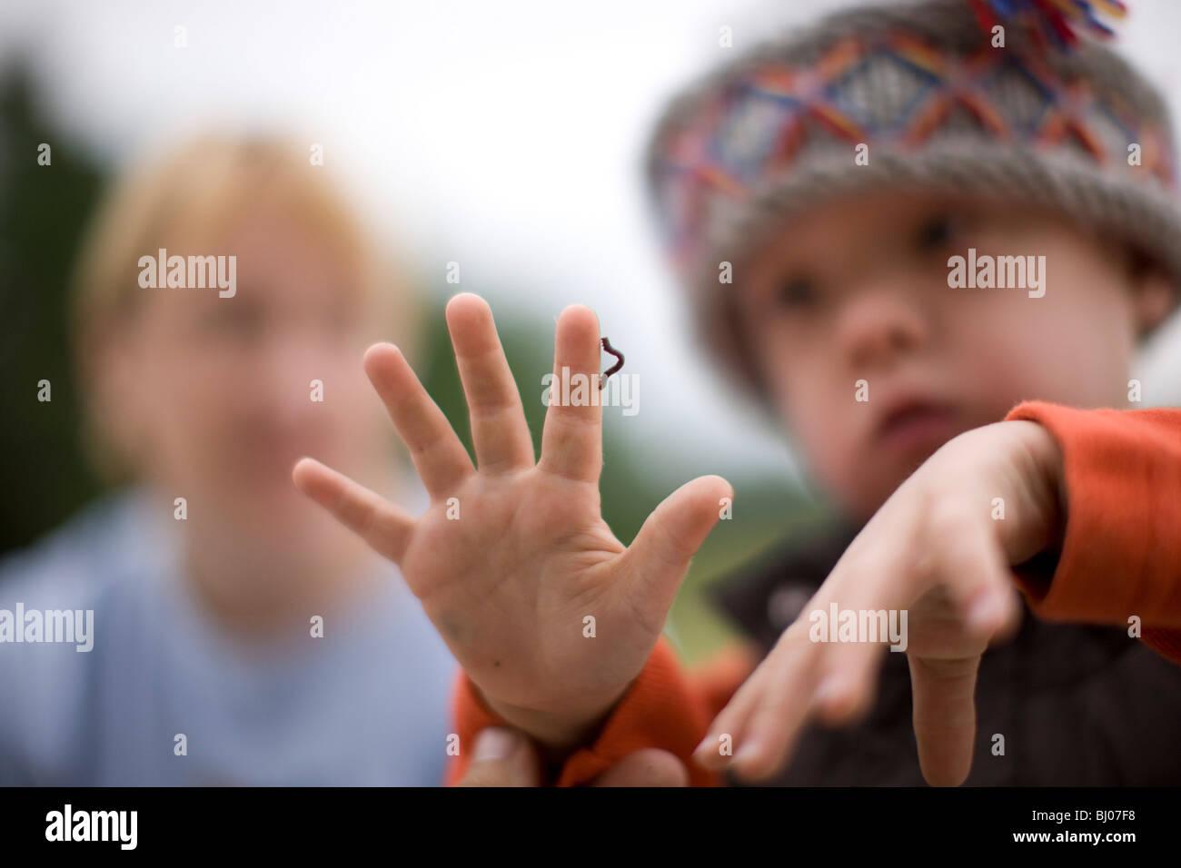 Ragazzo che guarda ad un inchworm strisciando sulla sua mano. Foto Stock