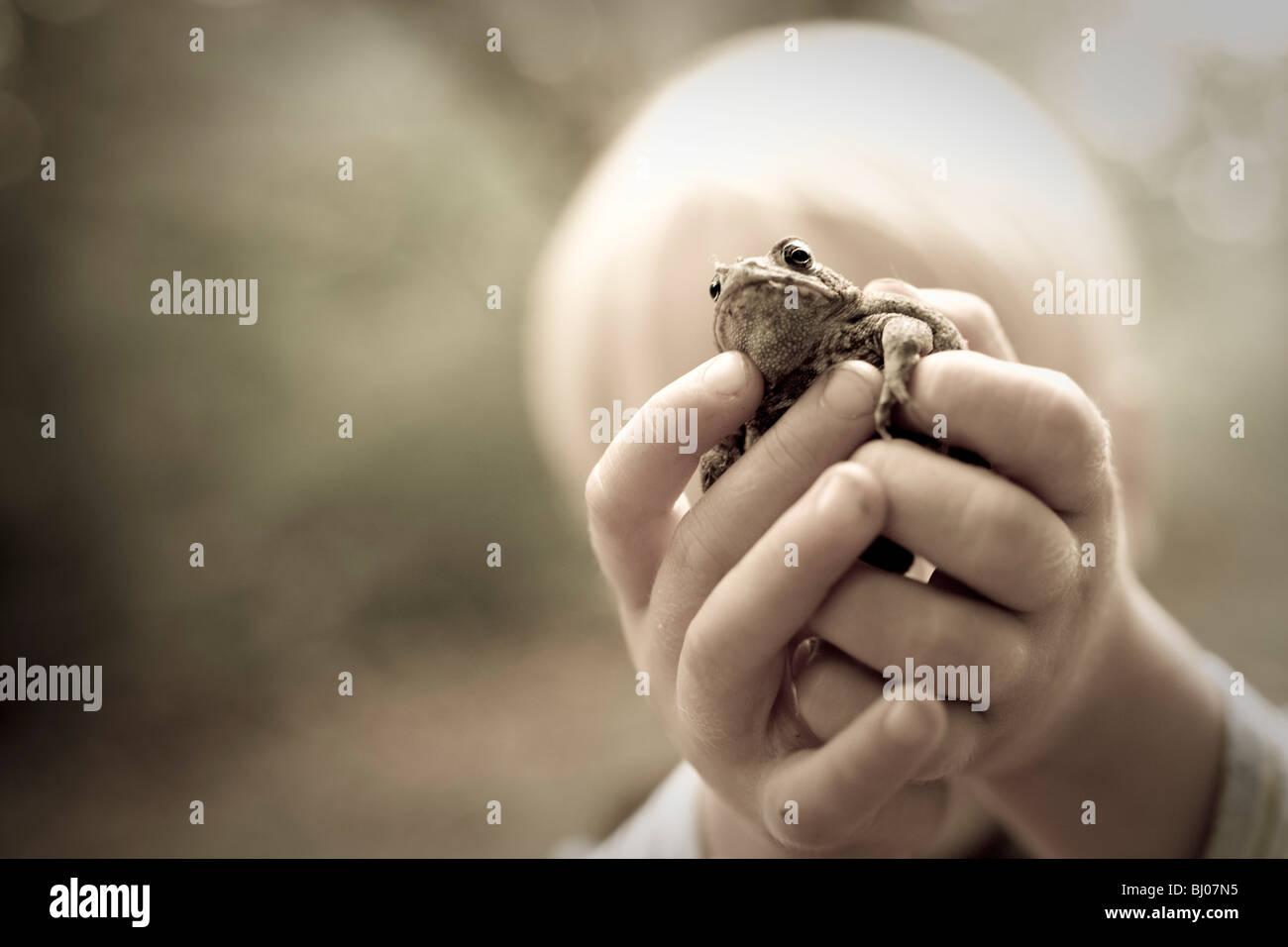 Un giovane bambino tenendo in mano un rospo. Immagini Stock