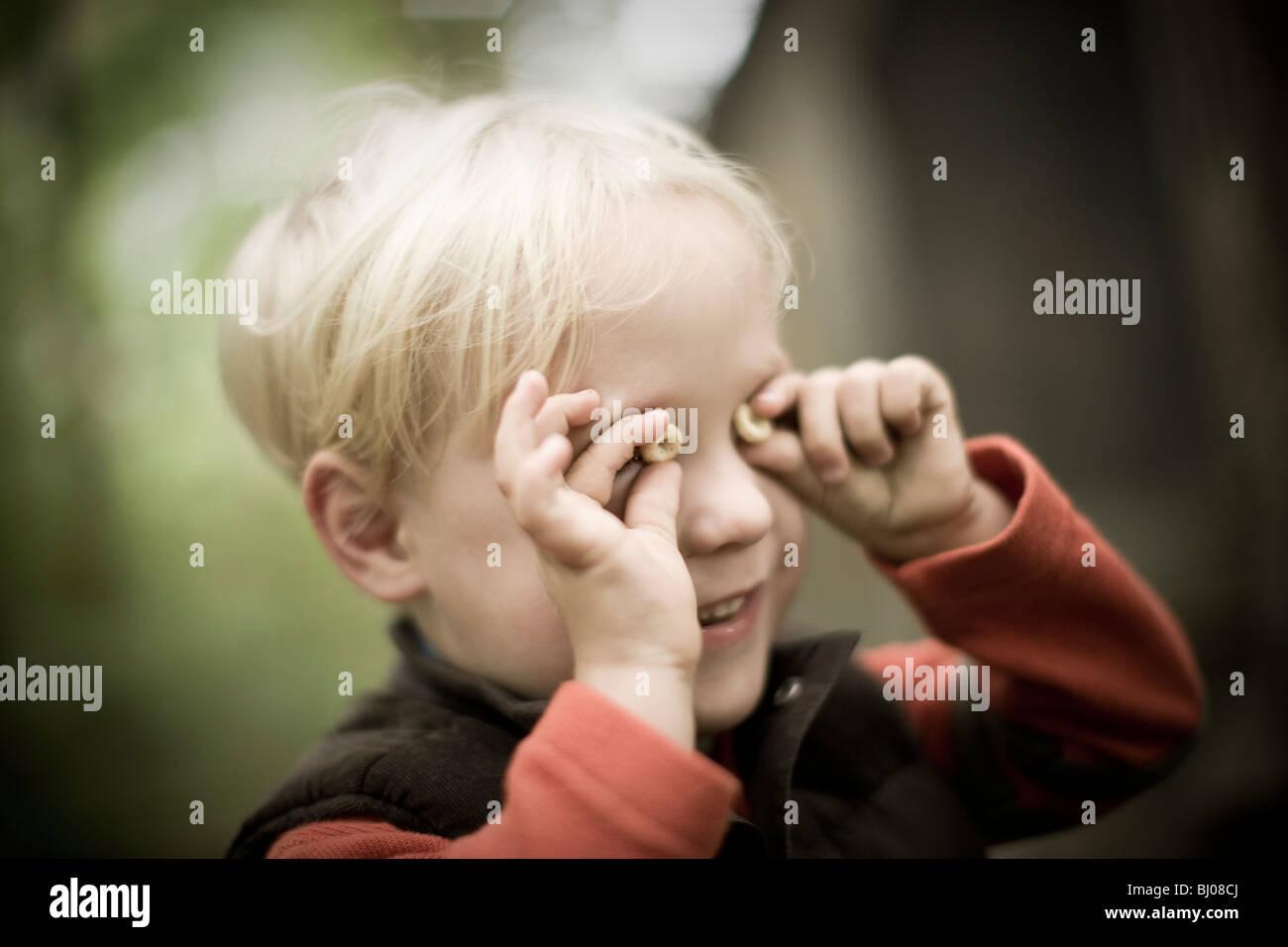 Giovane ragazzo giocando con cereali. Immagini Stock