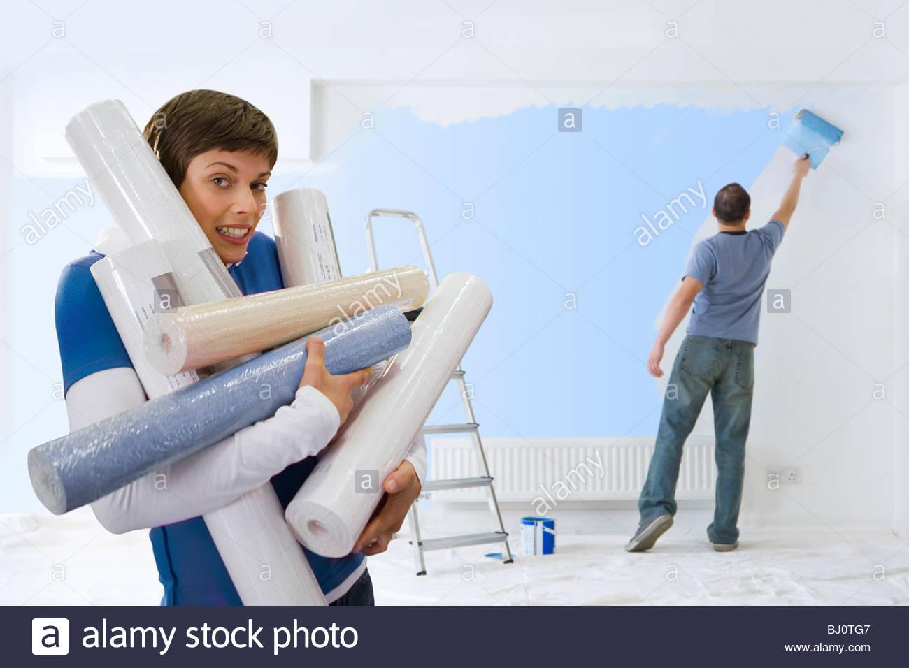 Donna che trasportano bracciata di sfondo mentre il marito dipinge Immagini Stock