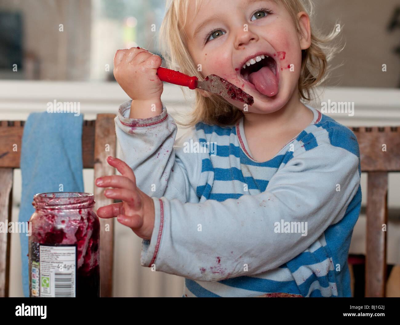 Un giovane ragazzo con la mancanza di educazione, sorrisi come egli lambisce inceppamento dal suo coltello al tavolo Immagini Stock