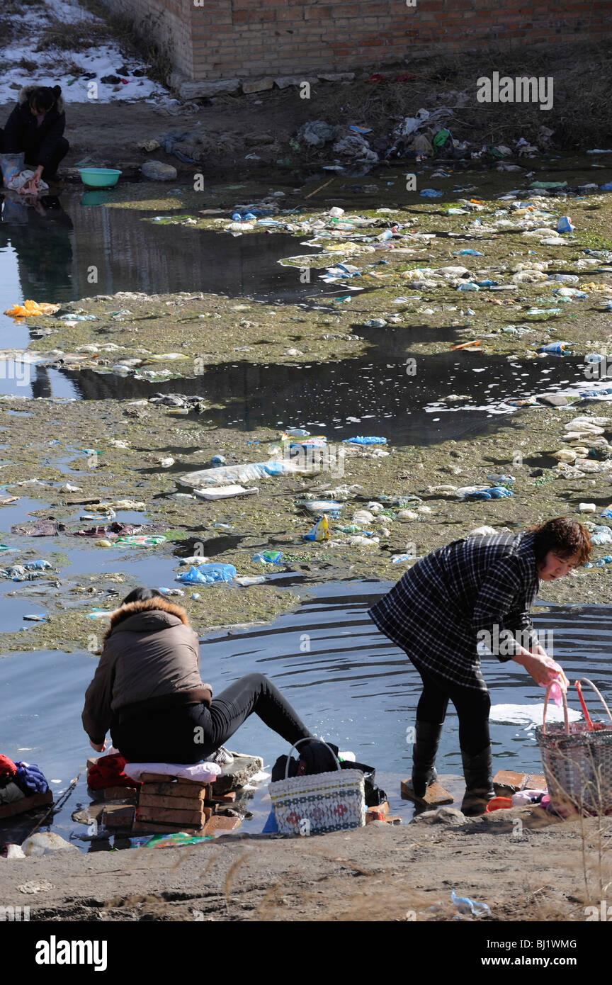 Le donne a lavare i panni in un stagno inquinato in un paesino della provincia di Hebei, Cina. 02-Mar-2010 Immagini Stock