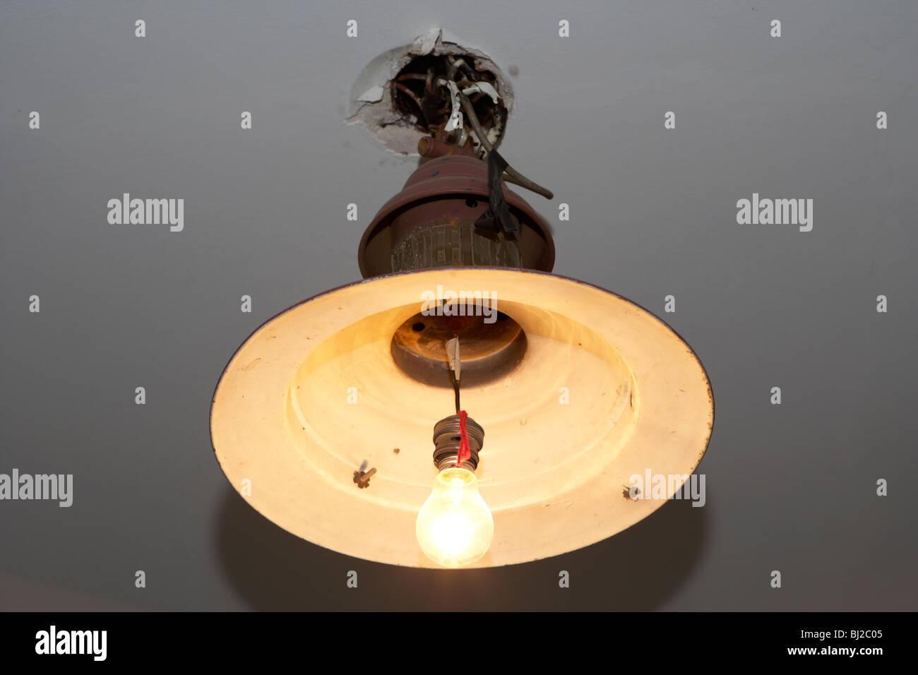 Vecchio pericoloso dodgy cablaggio luce a soffitto con bulbo nudo Immagini Stock