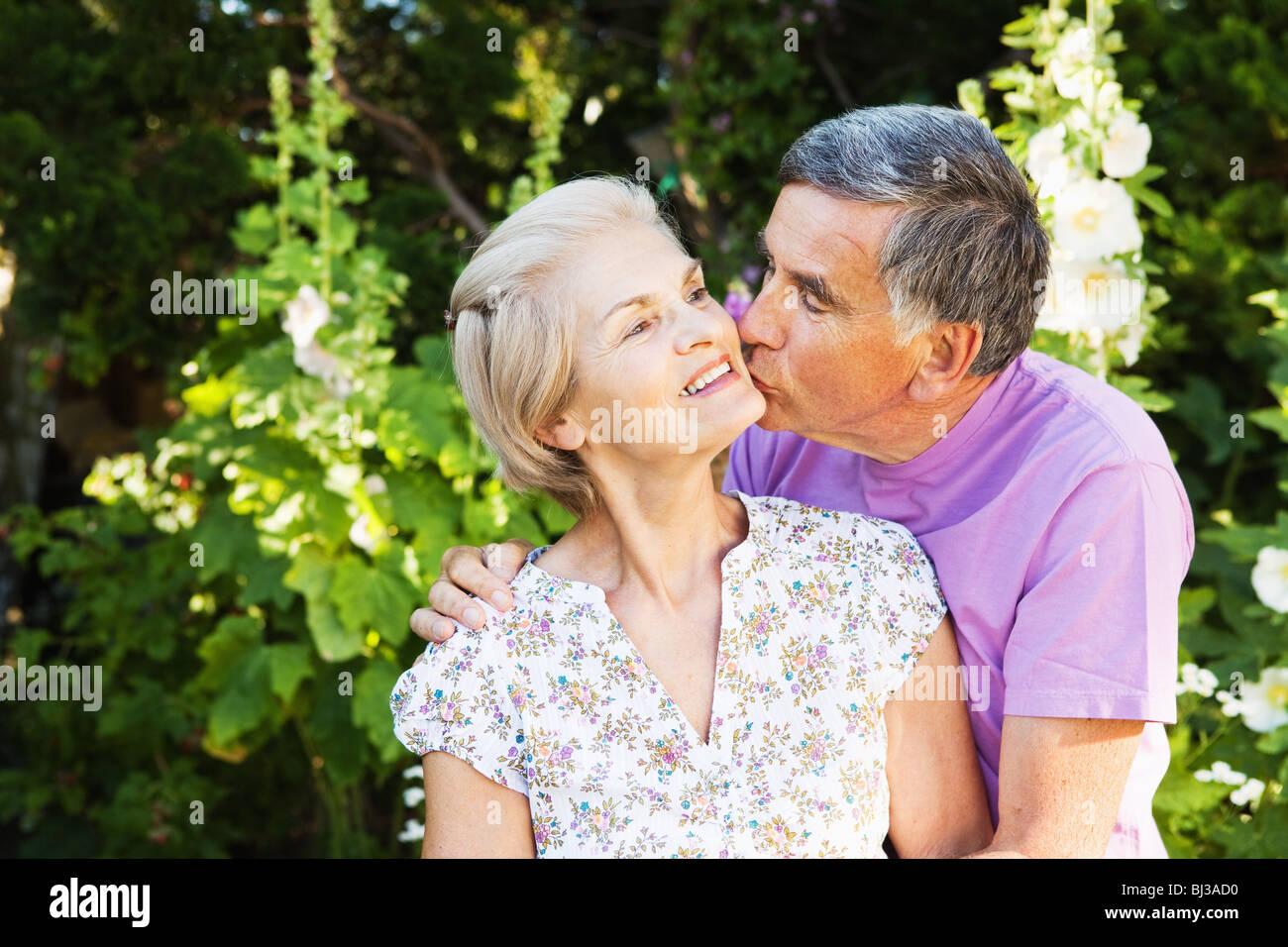 Uomo maturo baci donna matura. Immagini Stock