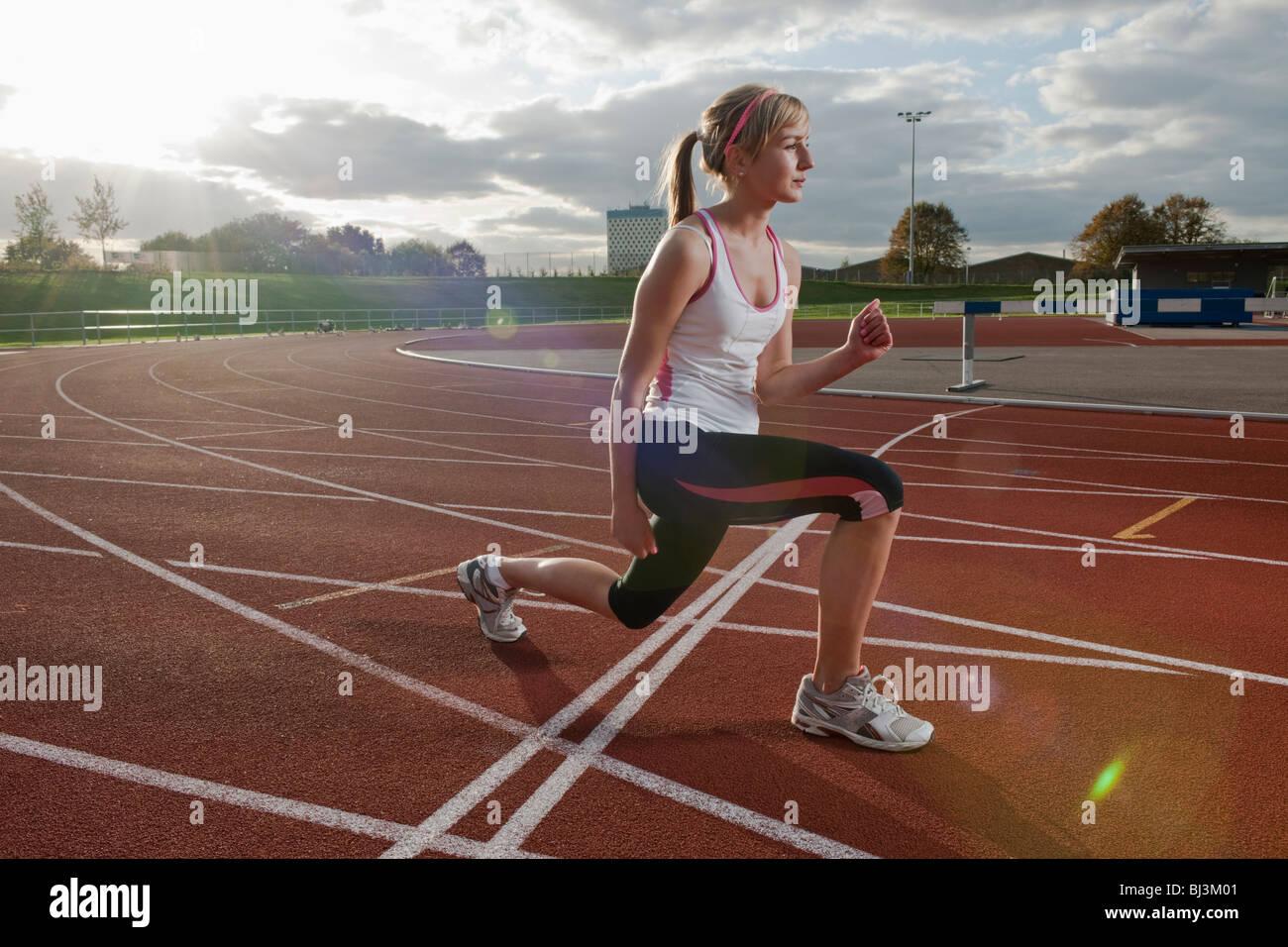 Atleta femminile stiramento dei muscoli delle gambe Immagini Stock