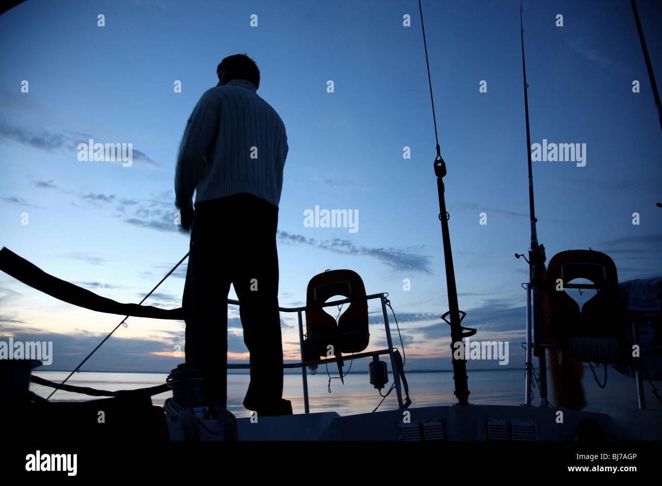 L'uomo angling su una barca a vela Immagini Stock