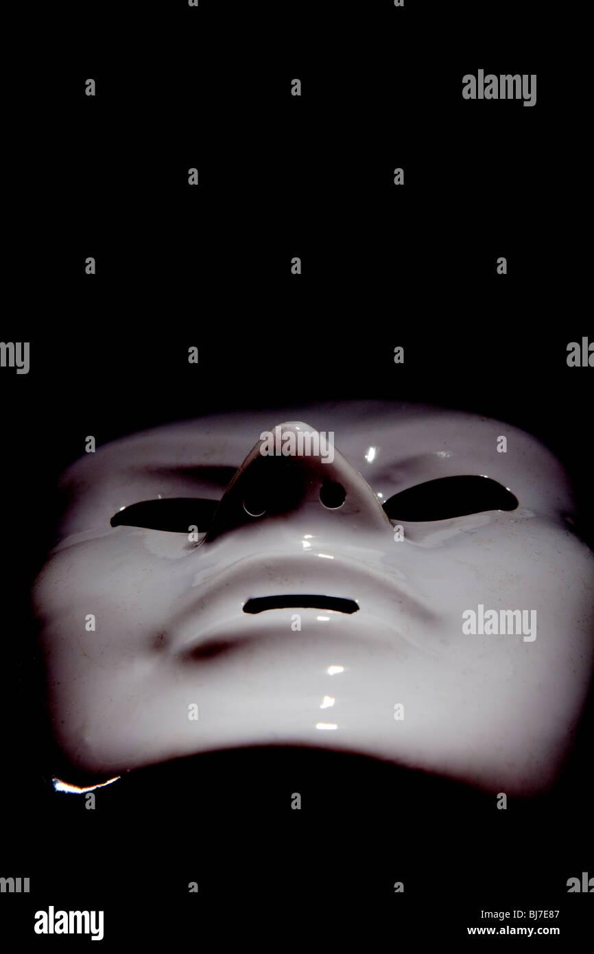 Maschera bianca su sfondo nero, l'uomo affronta Immagini Stock