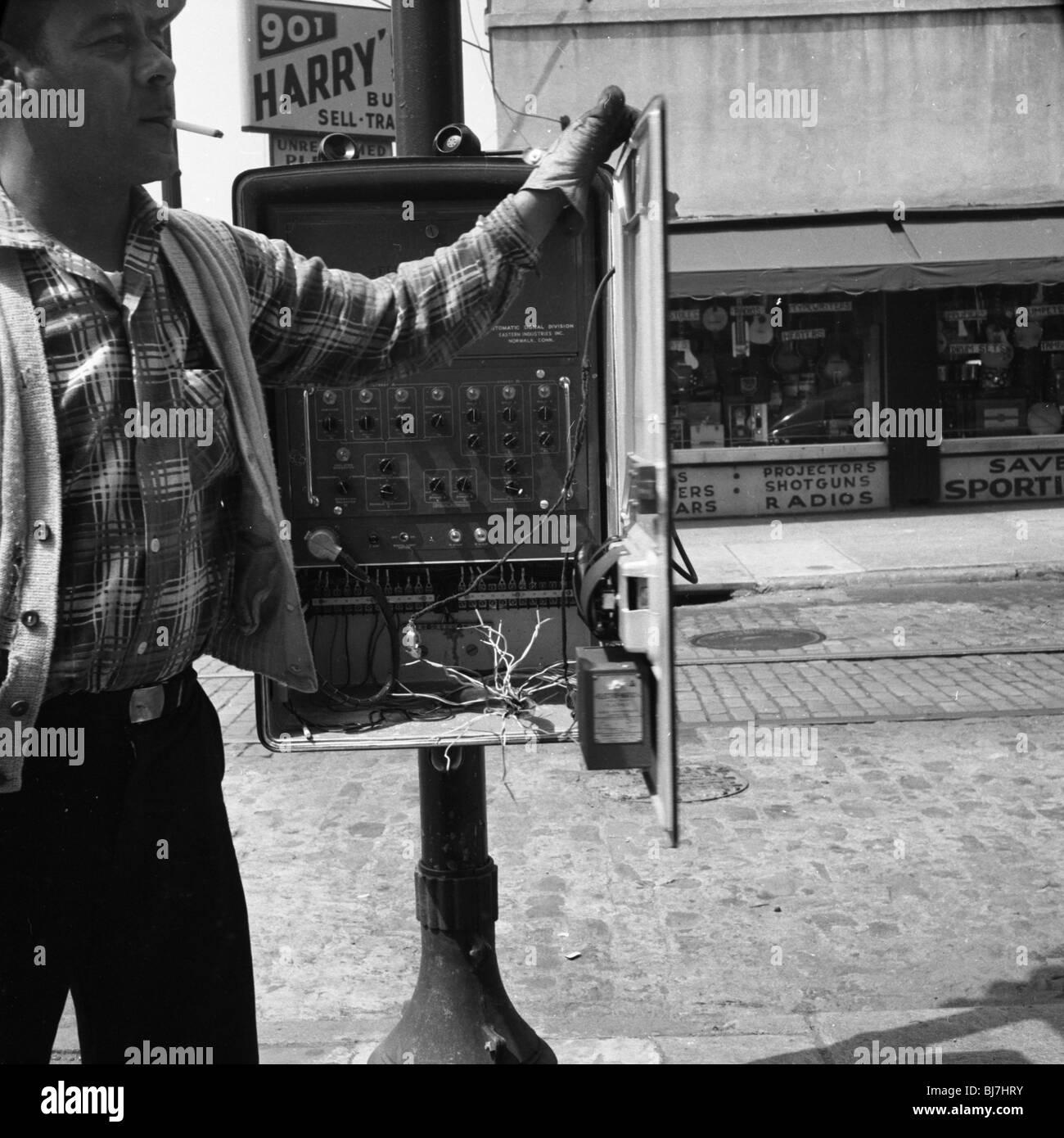 Una compagnia telefonica lavoratore con sigaretta penzolante lavora a Philadelphia durante il 1960s. blu collare Immagini Stock