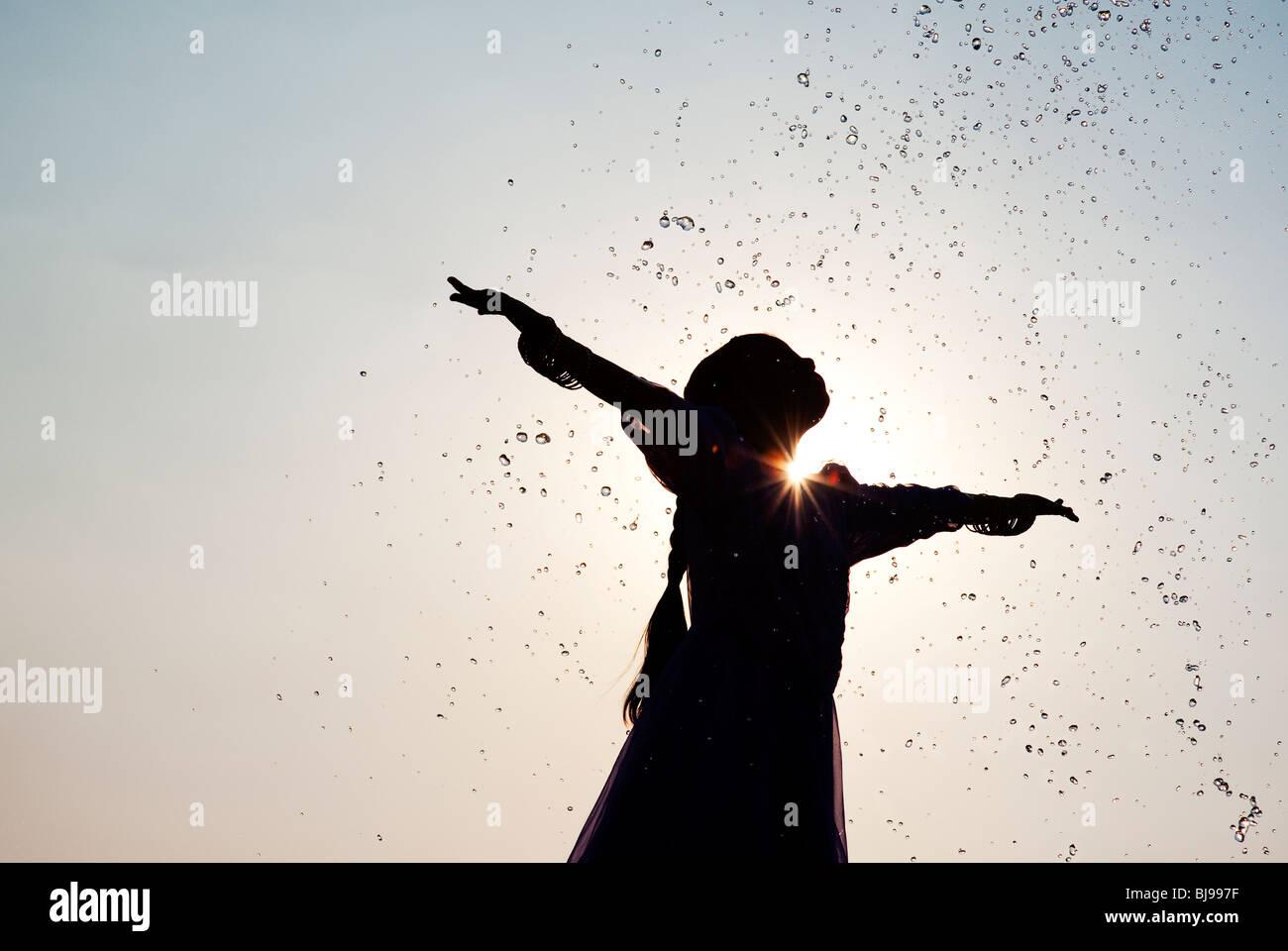 Silhouette di una giovane ragazza indiana godendo di essere spruzzato con acqua. India Immagini Stock