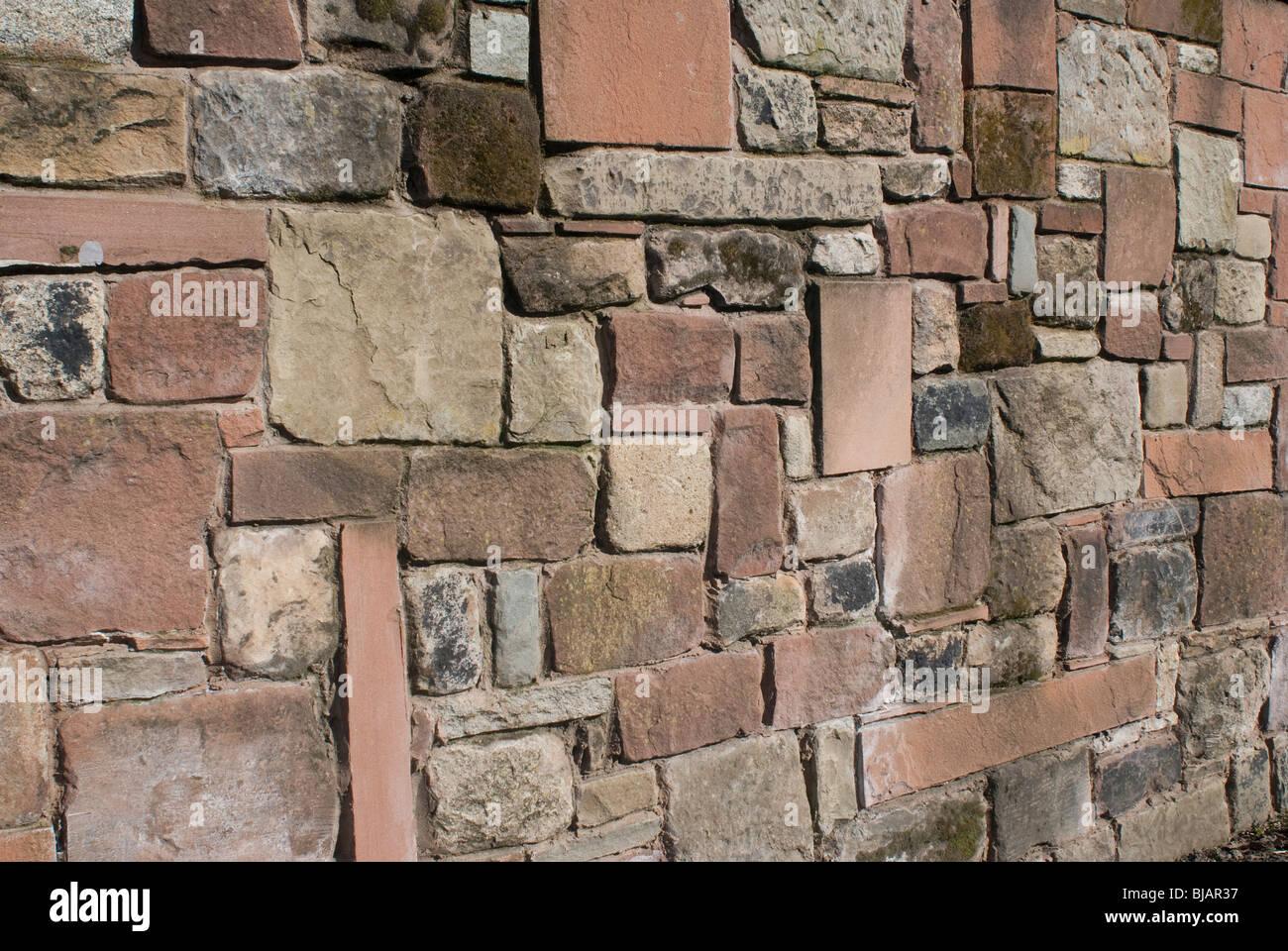 Un solido muro di pietra di pietra arenaria calcare e granito. Immagini Stock