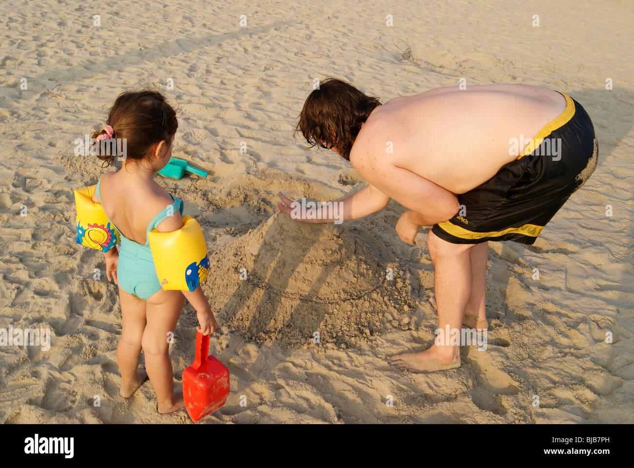 Carina ragazza turistica con suo padre la costruzione di un bel palazzo in riva mare sand.padre e figlia giocando a Kovalam Beach India Foto Stock