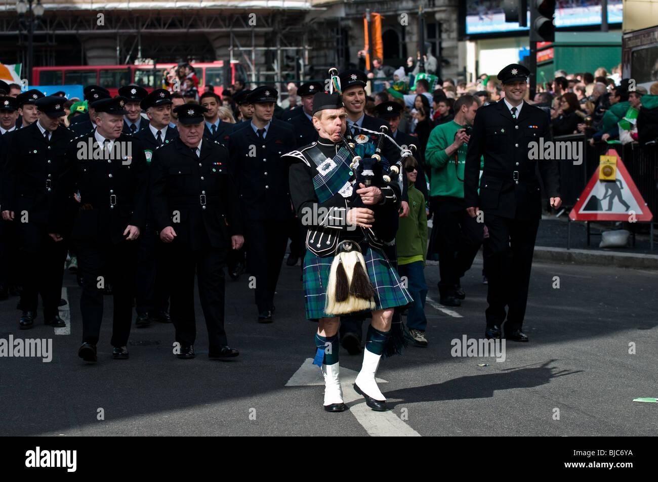 Un piper che conduce a una sfilata di vigili del fuoco durante la Festa di San Patrizio Parade di Londra. Foto Stock
