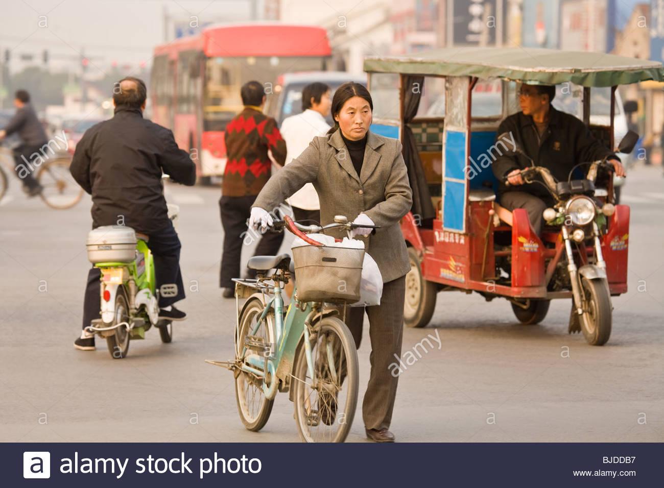 Donna con bicicletta attraversando la strada nel traffico caotico di Suzhou, provincia dello Jiangsu, Cina e Asia Immagini Stock