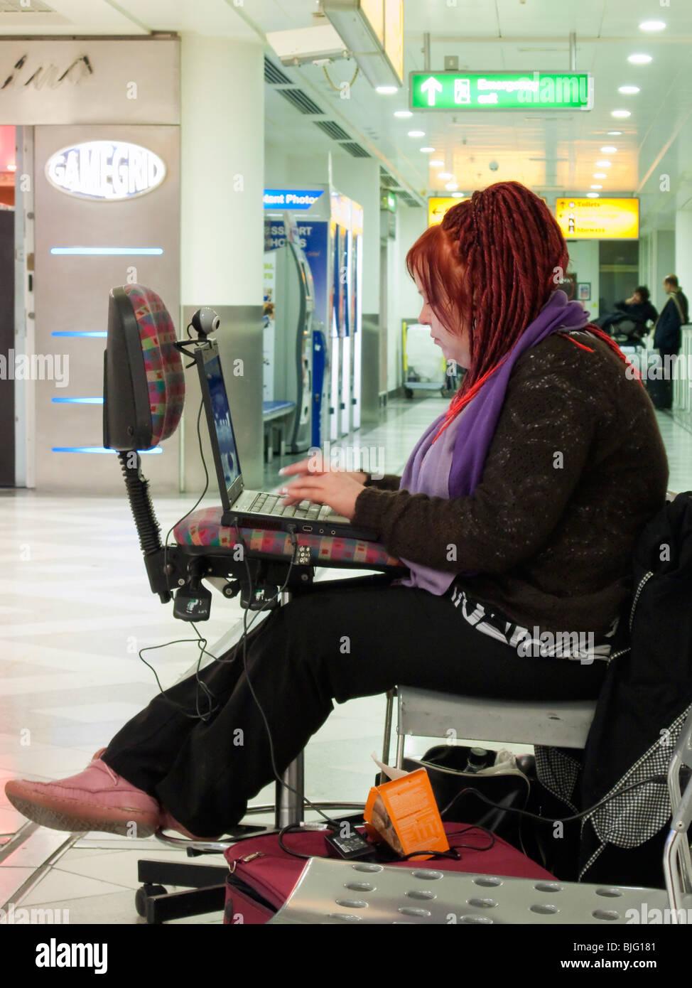 Una femmina di linea aerea passeggero utilizzando un computer portatile in un aeroporto zona di transito con l'attesa Immagini Stock