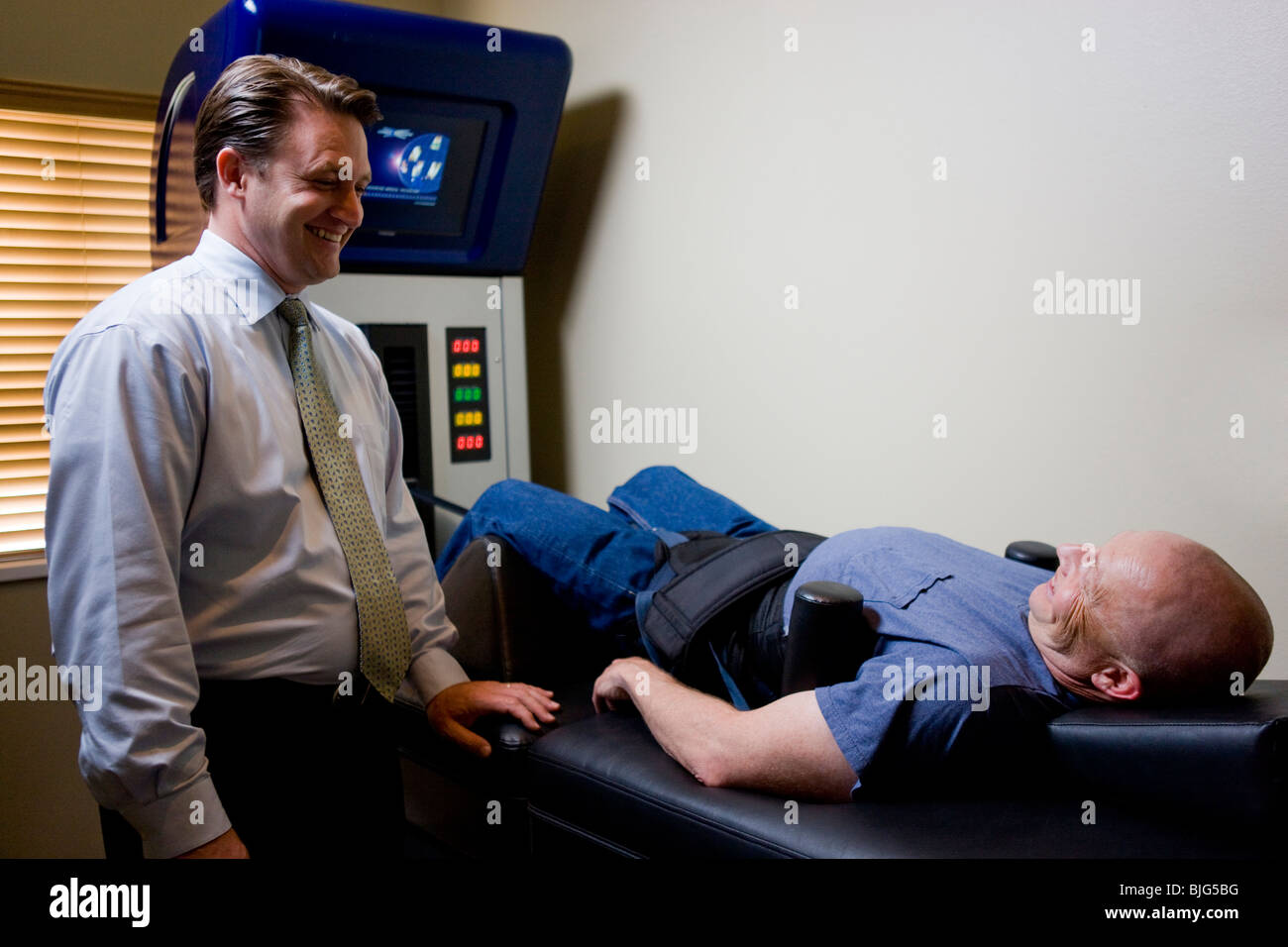 Uomo di ottenere il trattamento su una macchina chiropratica Immagini Stock
