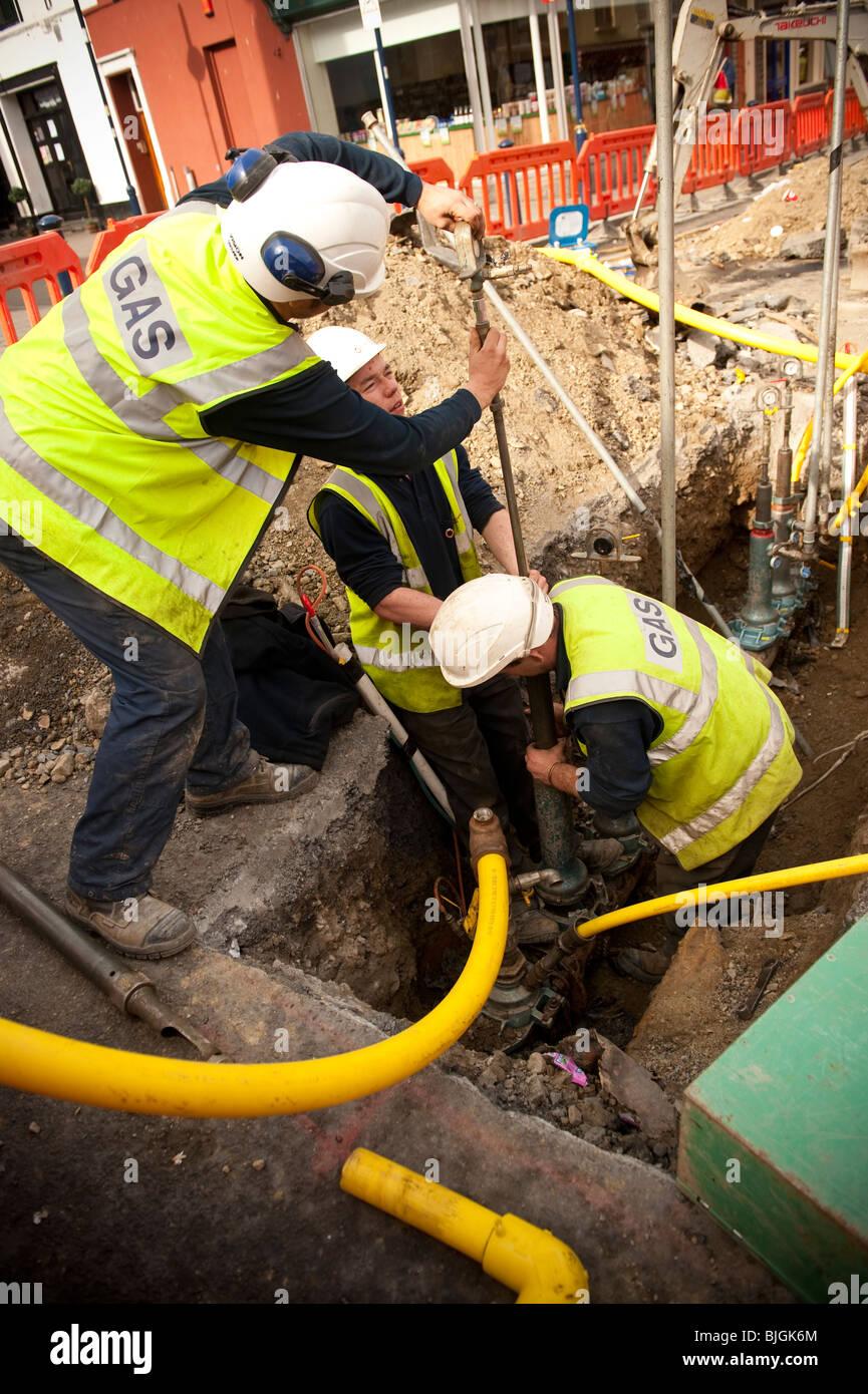 Gli ingegneri della British Gas di sostituzione di un gas in acciaio principale di alimentazione con un giallo tubo Immagini Stock