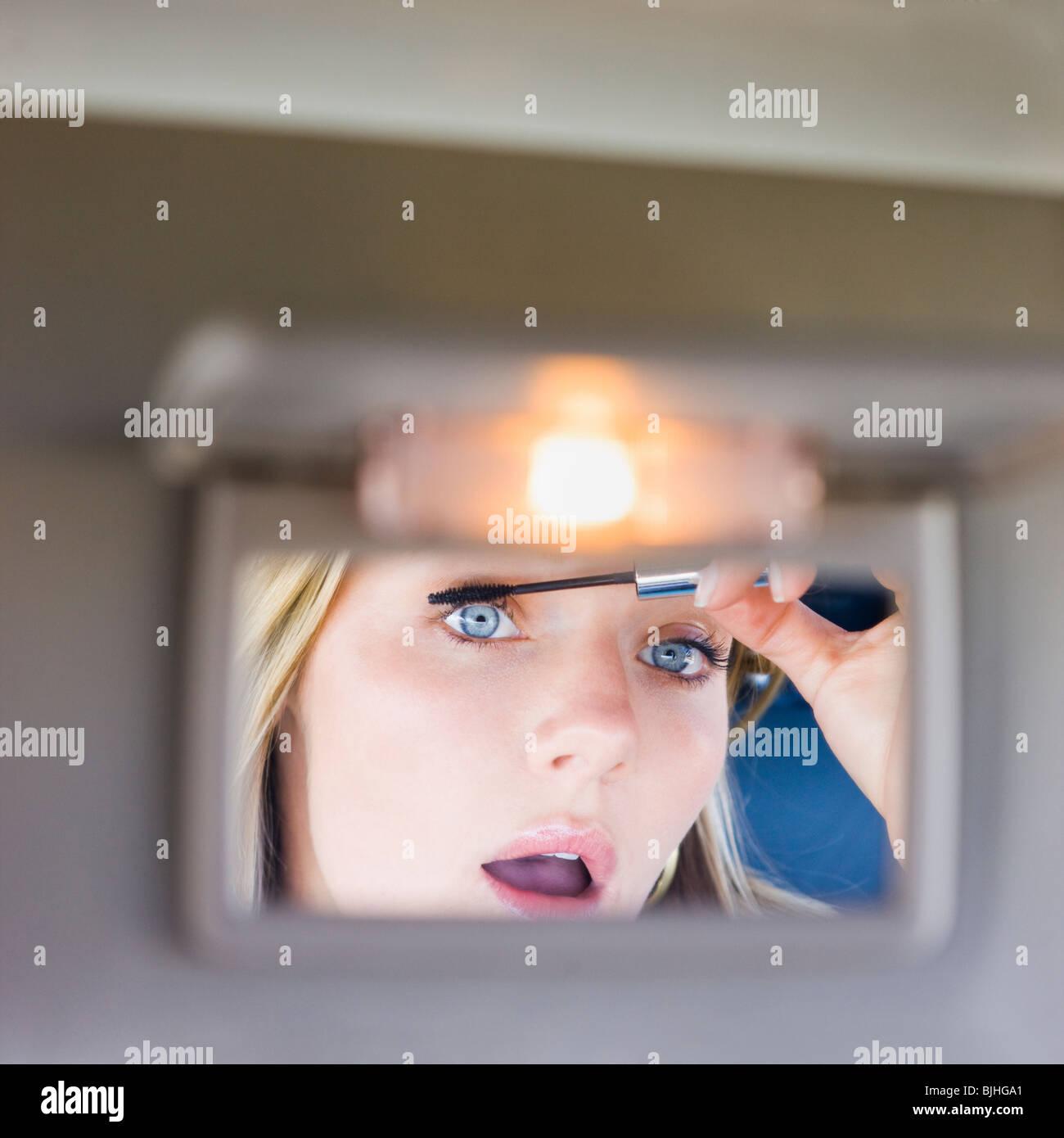 Donna mettendo sul trucco nella visiera specchio della vettura Immagini Stock