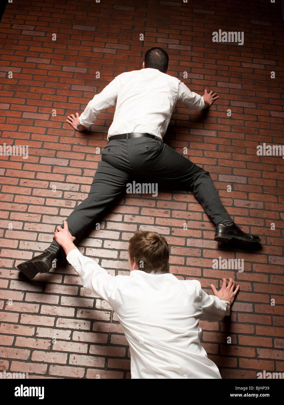 L'uomo salendo su un muro di mattoni mentre un altro uomo afferra sulla sua gamba Immagini Stock